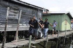 Villagers carry the body of a dead gunmen that was killed on Saturday for removal at Simunul village in Sabah's Semporna district. Reuters Photo