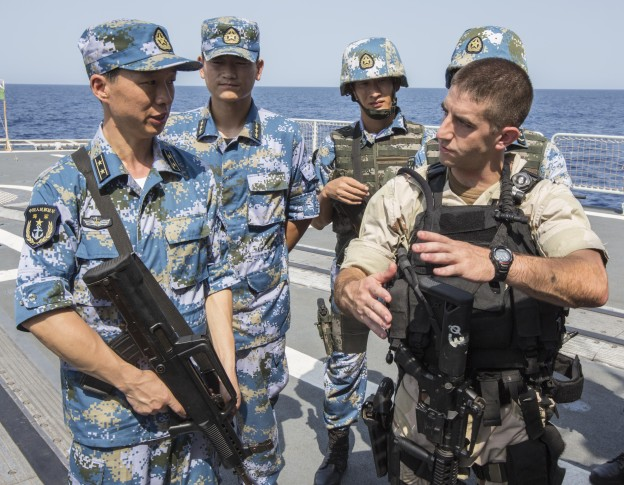 Lt. j.g. Jeffrey Fasoli, gunnery officer aboard the guided-missile destroyer USS Mason (DDG-87), discusses techniques with Chinese sailors aboard the People's Liberation Army (Navy) destroyer Harbin on Aug. 24, 2013.