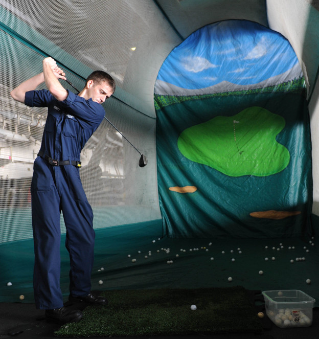 A sailors hits golf balls in an inflatable driving range during a Morale, Welfare and Recreation (MWR) event in the hangar bay of the aircraft carrier USS Dwight D. Eisenhower (CVN-69) in 2012. US Navy Photo