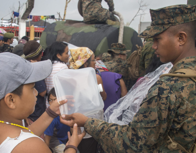 U.S. Marine Pfc. John Evans assigned to Combat Logistics Battalion 4 (CLB 4) distributes water on Nov. 23, 2013 to Palo residents affected by Typhoon Haiyan. US Navy Photo