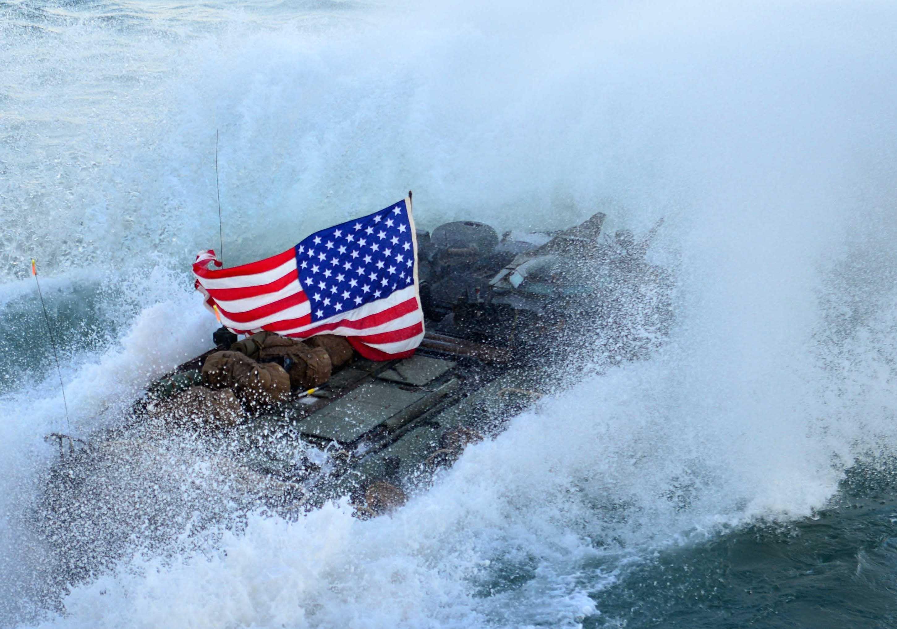 An amphibious assault vehicle (AAV) exits the well deck of the amphibious dock landing ship USS Carter Hall (LSD-50). US Navy Photo