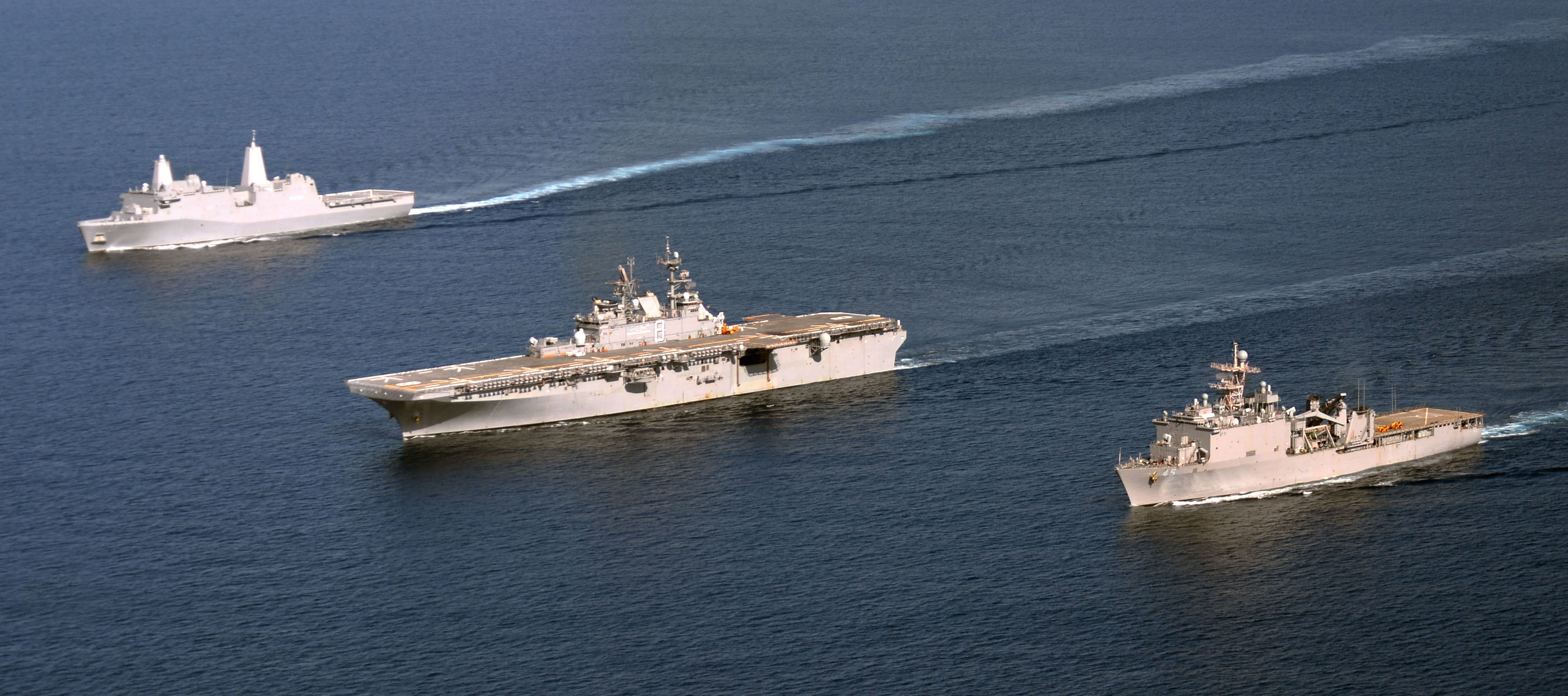 USS Makin Island (LHD-8), alongside the dock landing ship USS Comstock (LSD-45), right, and the amphibious transport dock ship USS San Diego (LPD-22) on March 14, 2014. US Navy Photo
