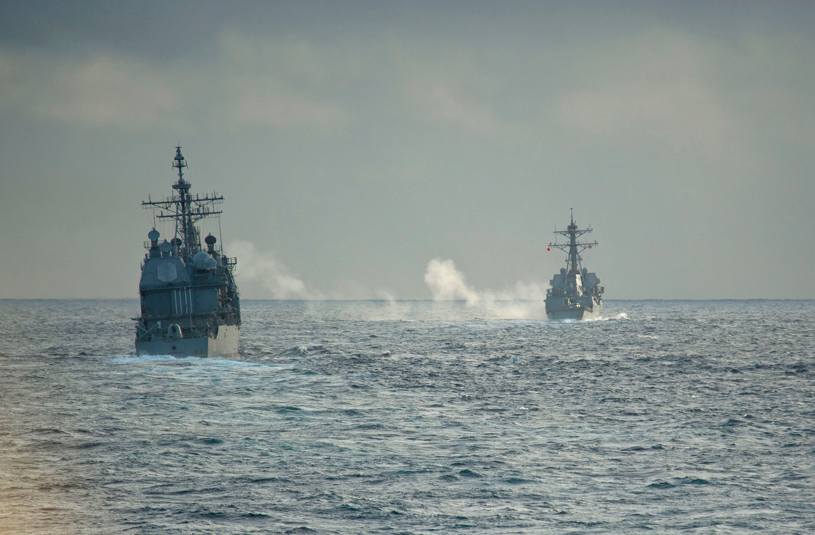 USS Philippine Sea (CG-58), right, fires a 5-inch gun during a live fire exercise with the guided-missile destroyers USS Truxton (DDG-103) on Feb. 20, 2014. US Navy Photo