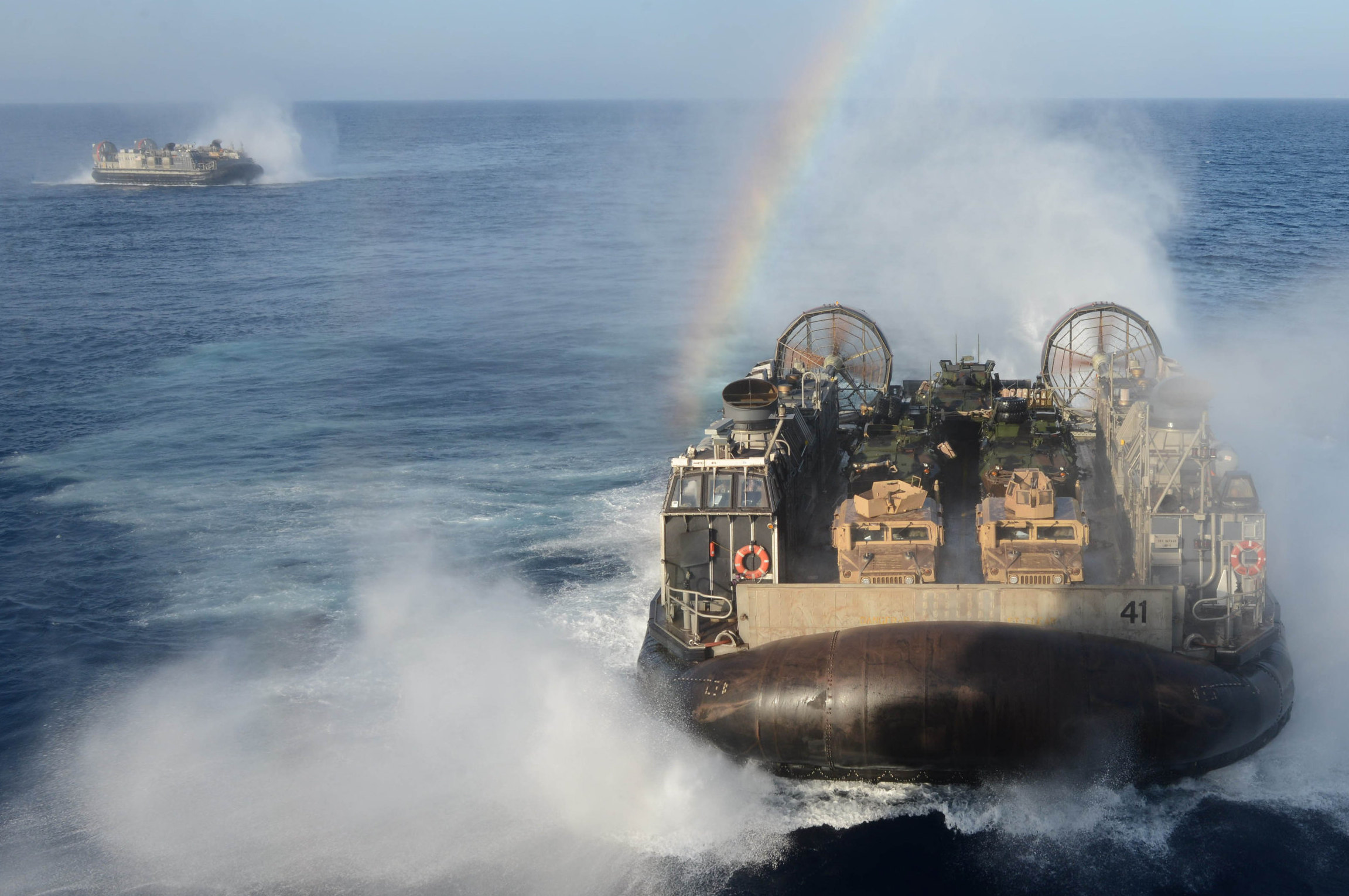 Landing craft air cushion (LCAC) vehicles from Assault Craft Unit (ACU) 4 approach the well deck of the multipurpose amphibious assault ship USS Bataan (LHD-5) on April 28, 2014. US Navy Photo