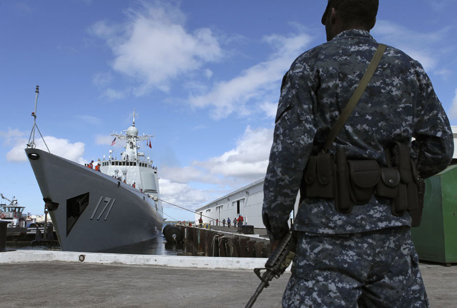 An American sailor on guard near the Chinese guided missile destroyer Haikou (171) at Naval Station Pearl Harbor, Hawaii on June 24, 2014. CCTV Photo