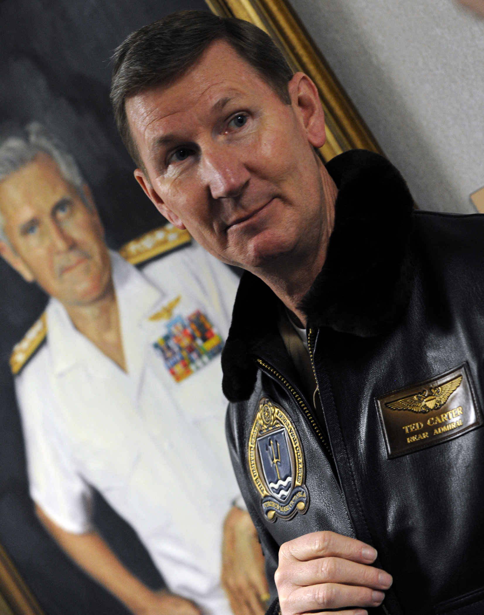 "Rear Adm. Walter E. ""Ted"" Carter Jr., president of the U.S. Naval War College stands in front of a portrait of Vice Adm. James B. Stockdale on Dec. 13, 2013. US Navy Photo"