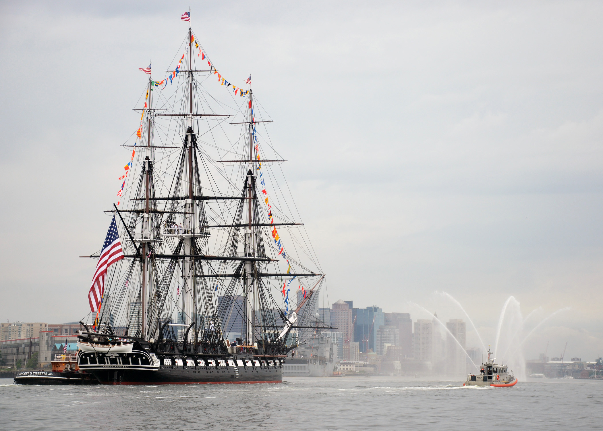 USS Constitution passes by downtown Boston during the ship's Independence Day underway. US Navy Photo