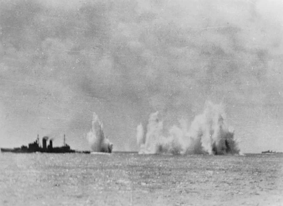 The Royal Navy cruiser HMS Exeter (68) and the Australian cruiser HMAS Hobart (D63) under aerial attack by Japanese aircraft in seas of South East Asia. A Dutch destroyer is visible at right. Most probably this image was taken as the ship was passing through the Gaspar Straights, Indonesia, 14-15 February 1942. Imperial War Museums Photo