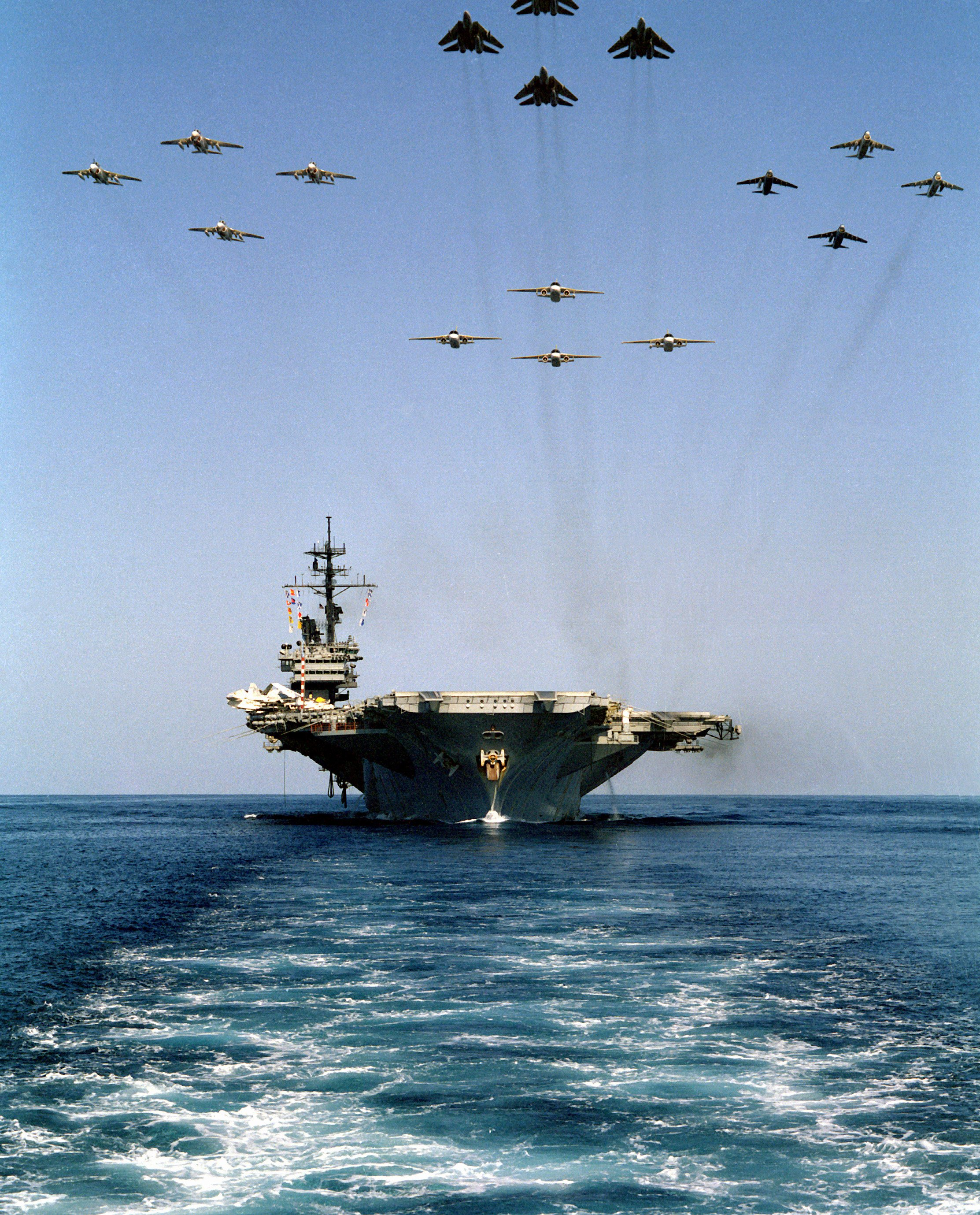 USS AMERICA (CV-66) underway as16 aircraft from Carrier Air Wing One (CVW-1) fly overhead in 1983. US Navy Photo