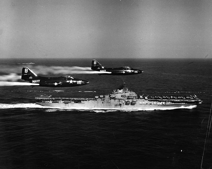 F-9F Fighters zoom by USS Princeton (CV-37) in 1951. US Navy Photo