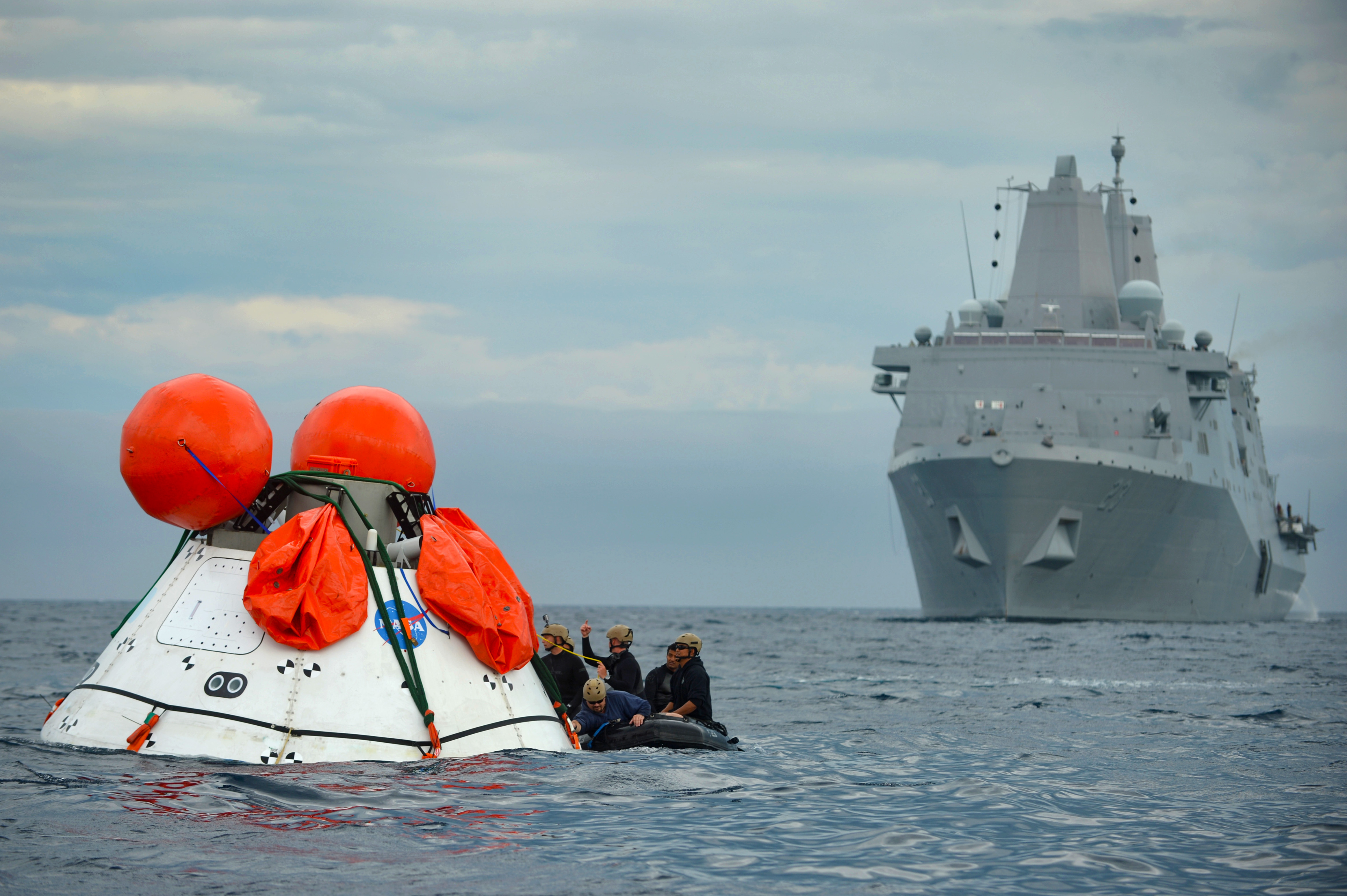 Sailors from the amphibious transport dock ship USS Anchorage (LPD 23) and Navy divers assigned to Explosive Ordnance Disposal Mobile Unit (EODMU) 11, Mobile Diving and Salvage Company 11-7, participate in the second underway recovery test for the NASA Orion Program on Aug. 3, 2014. US Navy Photo