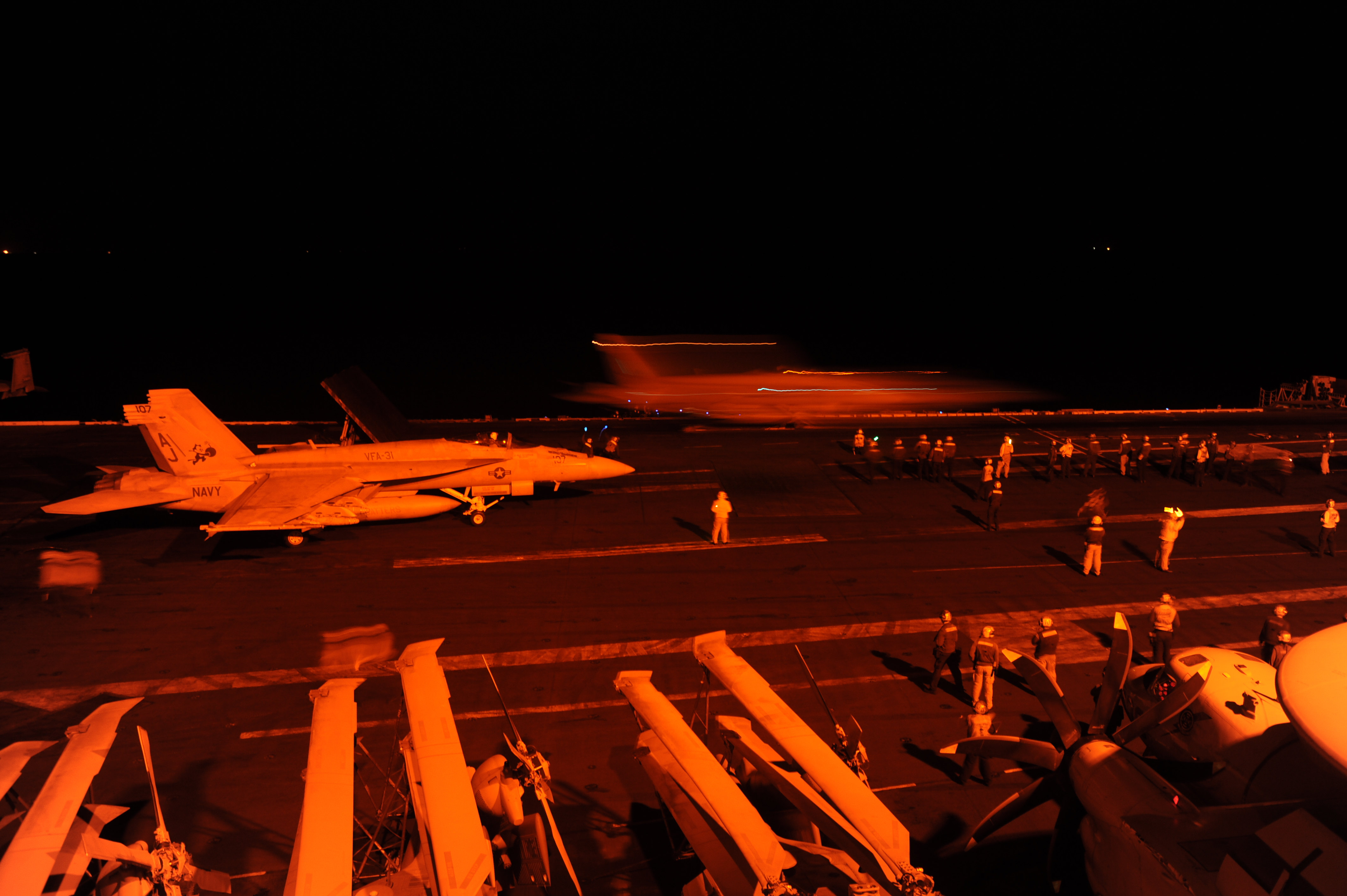 F/A-18E Super Hornet, attached to Strike Fighter Squadron (VFA) 31, and an F/A-18F Super Hornet, attached to Strike Fighter Squadron (VFA) 213, prepare to launch from the flight deck of the aircraft carrier USS George H.W. Bush (CVN 77) to conduct strike missions against ISIS on Sept. 23, 2014. US Navy Photo