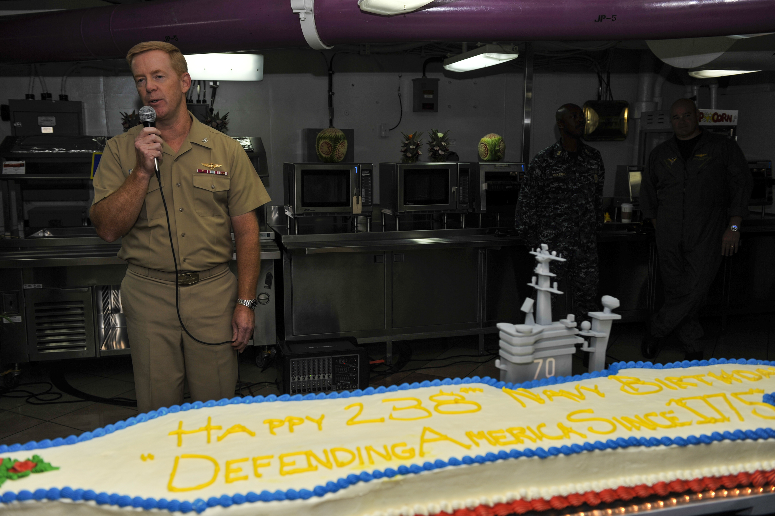 USS Carl Vinson's (CVN 70) commanding officer Capt. Kent Whalen address the crew during a cake cutting celebrating the Navy's 238th birthday. US Navy Photo