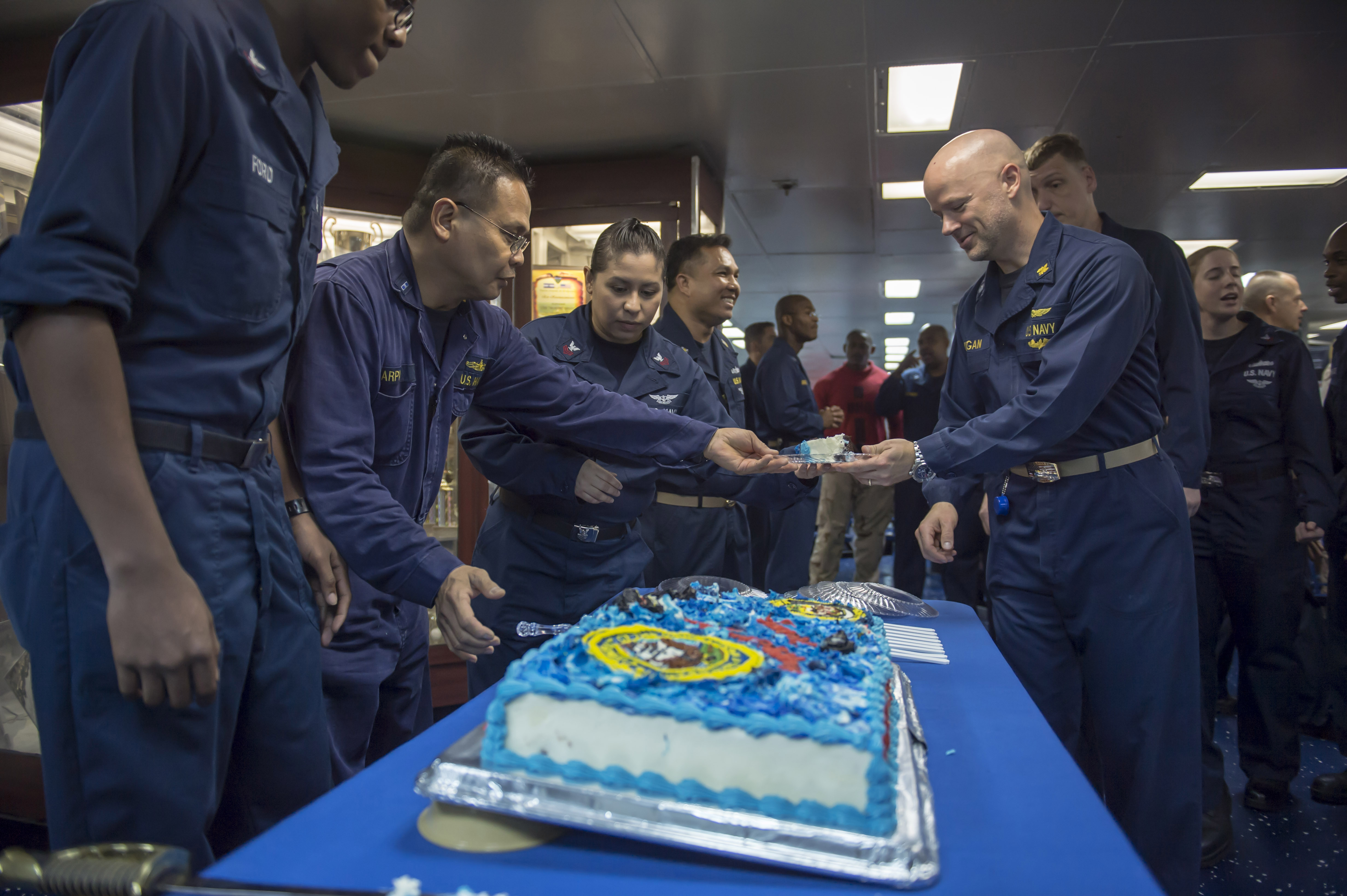 CWO Edwin Carpio hands out a piece of cake during a Navy birthday cake-cutting ceremony aboard the amphibious assault ship USS Boxer (LHD-4) in 2013.