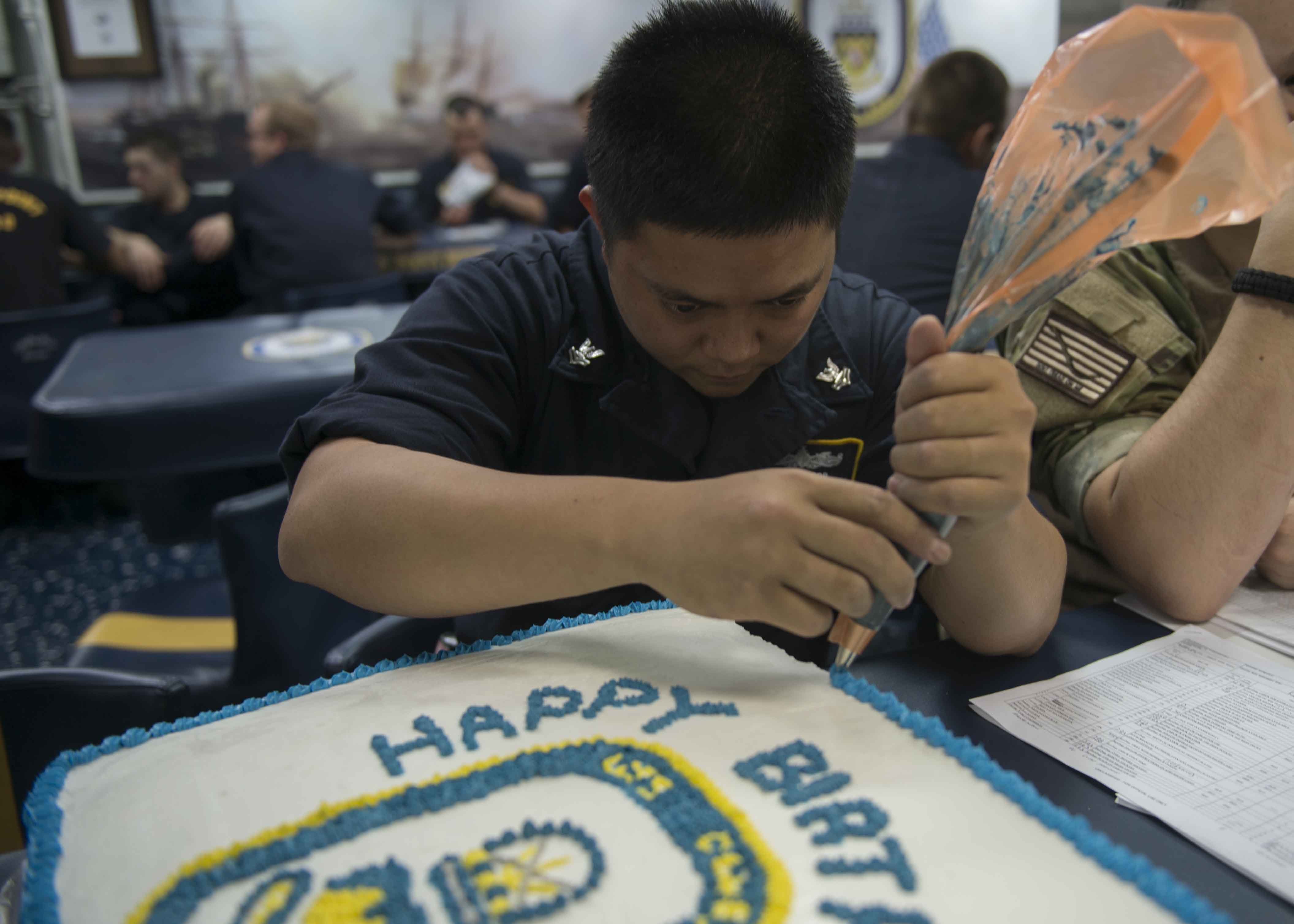 Culinary Specialist 2nd Class Ruel Jacob, from Grover Beach, Calif., decorates a cake for crew members in 2014. US Navy Photo