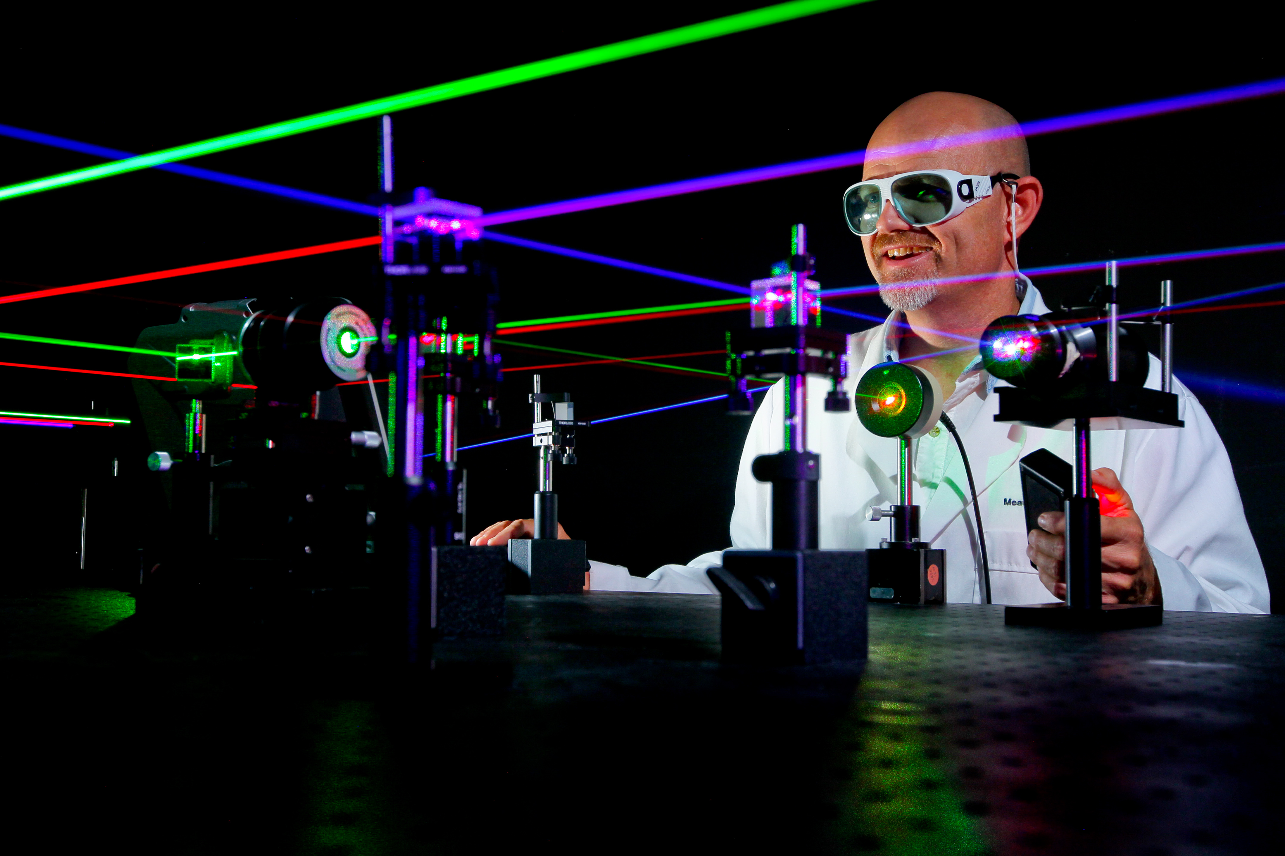 A microwave/electro-optic (MS32) electronics engineer at Naval Surface Warfare Center (NSWC), Corona Division, uses visible lasers to align various optical components on Aug. 29, 2014. US Navy Photo