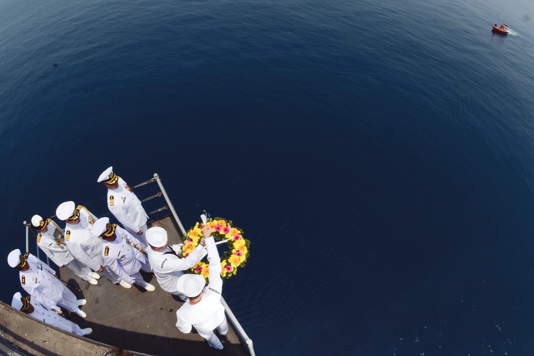 Sailors assigned to the submarine tender USS Frank Cable (AS 40) lower a wreath into the water as naval officers from Australia, Indonesia and the United States observe during a ceremony in honor of the crews of the U.S. Navy heavy cruiser USS Houston (CA 30) and the Royal Australian Navy light cruiser HMAS Perth (D29) on Oct. 14, 2014. US Navy Photo