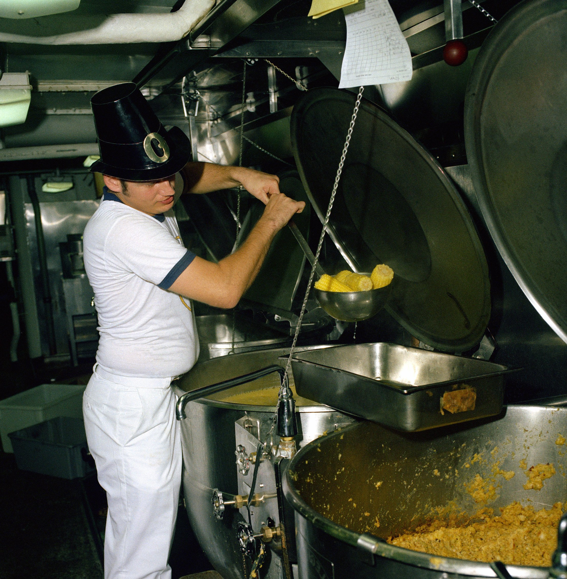 A mess management specialist helps prepare Thanksgiving dinner aboard the nuclear-powered aircraft carrier USS CARL VINSON (CVN-70) in 1984.