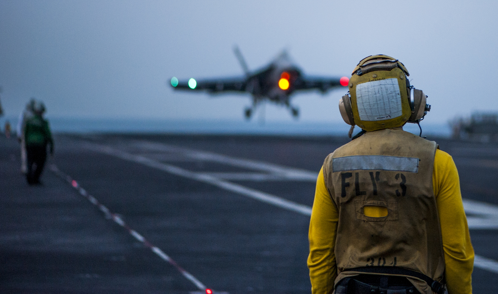 A sailor monitors the flight deck of the Nimitz-class aircraft carrier USS Carl Vinson (CVN-70). US Navy Photo