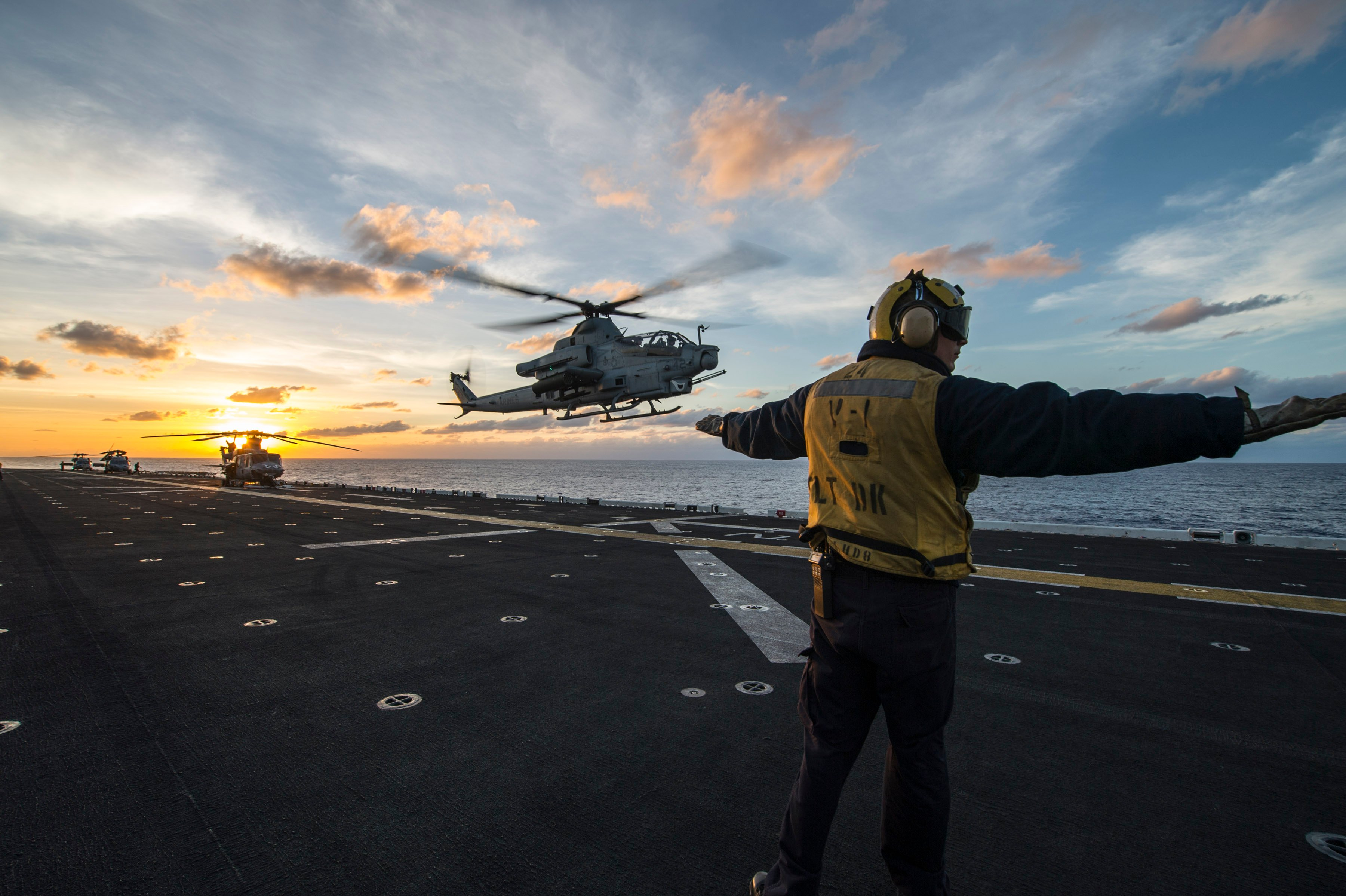 A Sailor signals an AH-1Z Viper helicopter attached to Marine Medium Tiltrotor Squadron (VMM) 163 (Reinforced) to land aboard the amphibious assault ship USS Makin Island (LHD 8) during routine flight operations in the Pacific Ocean on Feb. 4, 2015. US Navy Photo.