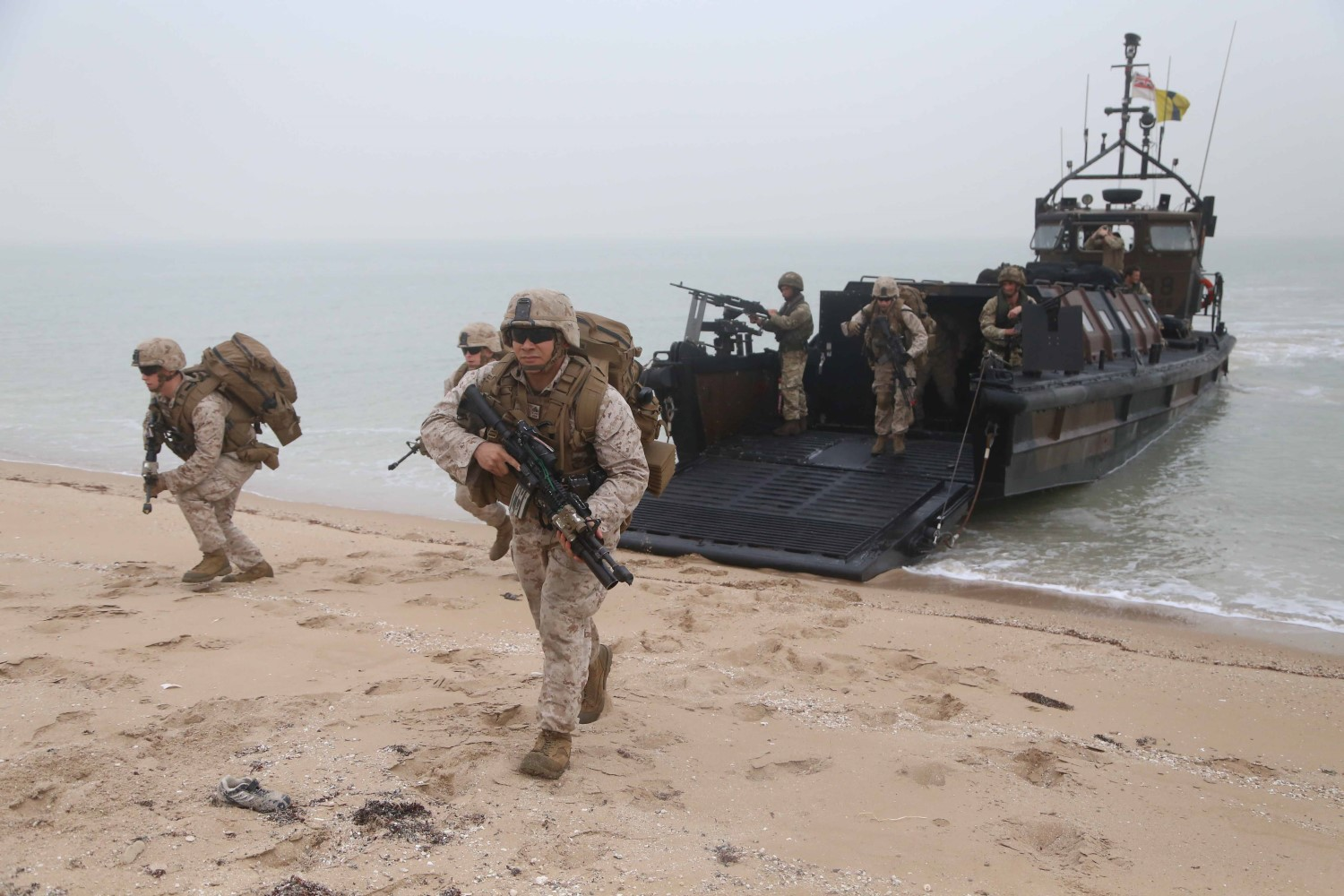 U.S. Marines with Fox Company, Battalion Landing Team 2nd Battalion, 1st Marines, 11th Marine Expeditionary Unit (MEU), disembark from a British landing craft vehicle personnel (LCVP) and rush toward their pre-designated security positions during Exercise Cougar Voyage 2015. US Marine Corps Photo
