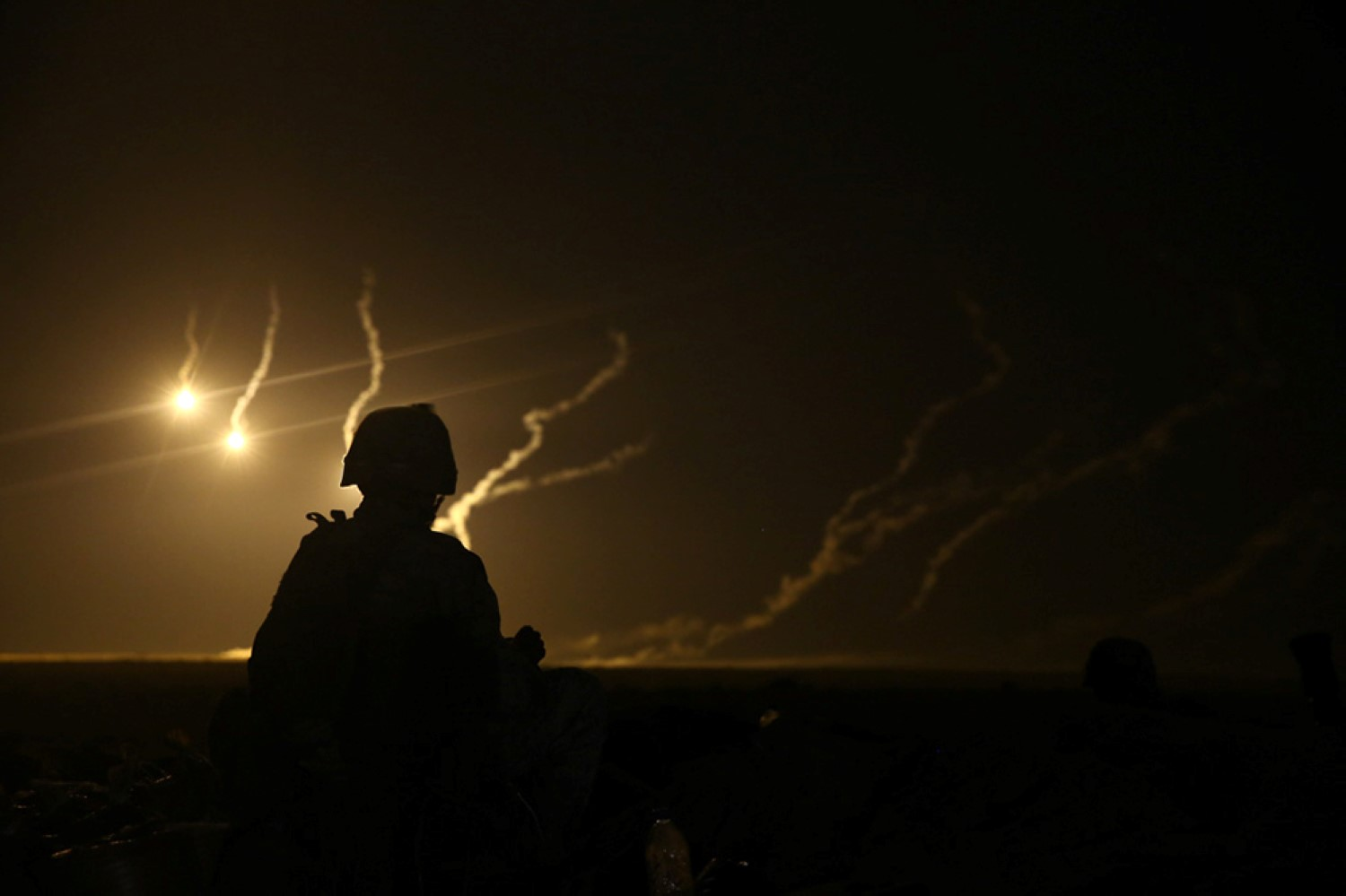 A U.S. Marine with Weapons Company, Battalion Landing Team 2nd Battalion, 1st Marines, 11th Marine Expeditionary Unit (MEU), watches 81mm illumination mortar rounds fall during a joint mortar range with Royal Saudi Naval Forces Marines. US Marine Corps Photo
