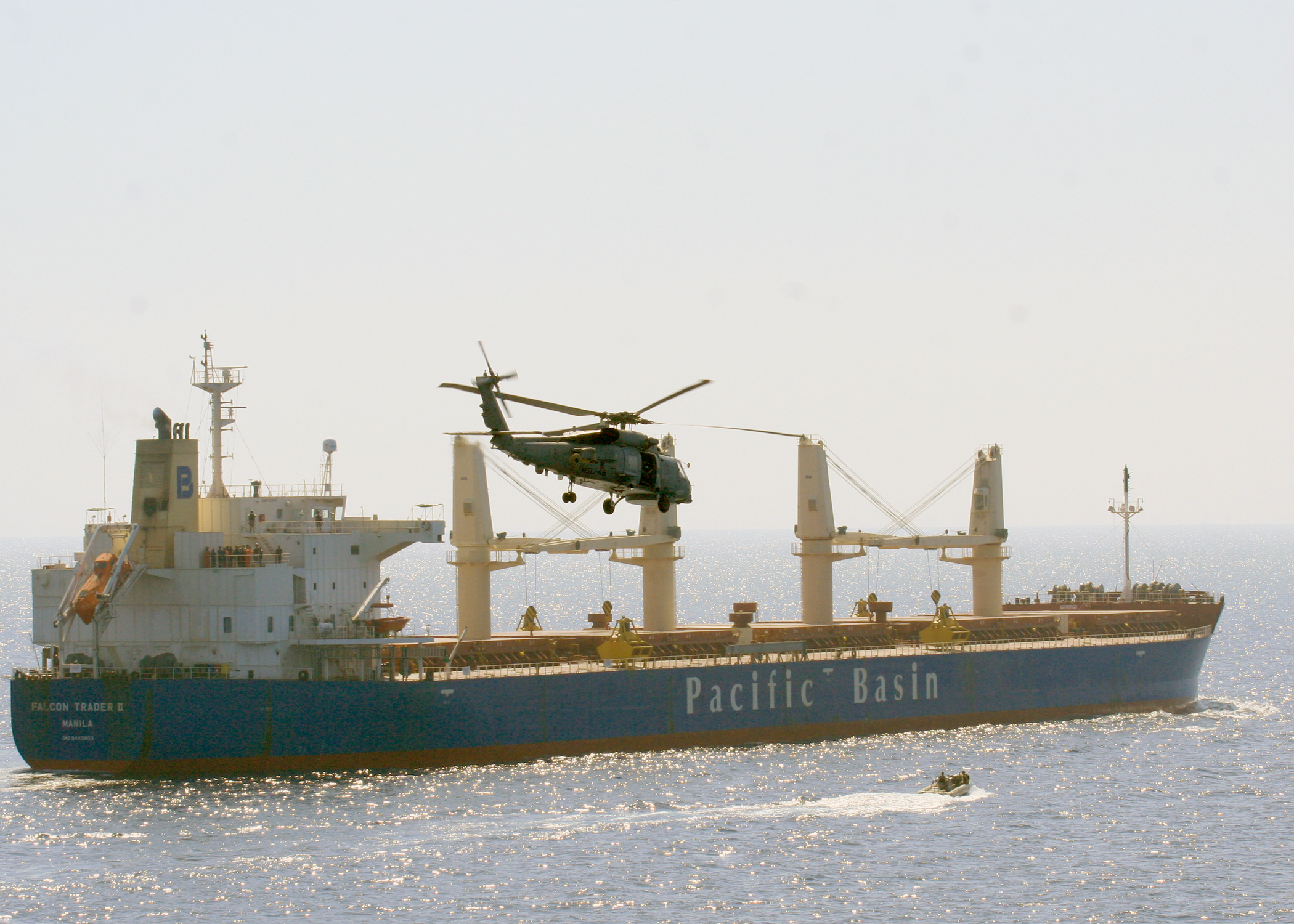 An SH-60B Sea Hawk helicopters from Helicopter Anti-Submarine Squadron Light (HSL) 48 embarked aboard the guided-missile cruiser USS Leyte Gulf (CG 55) and a rigid-hull inflatable boat from Leyte Gulf monitor the Philippine-flagged merchant vessel M/V Falcon Trader II, which had sent out a distress call reporting it had been boarded by pirates in March 2011. US Navy photo.
