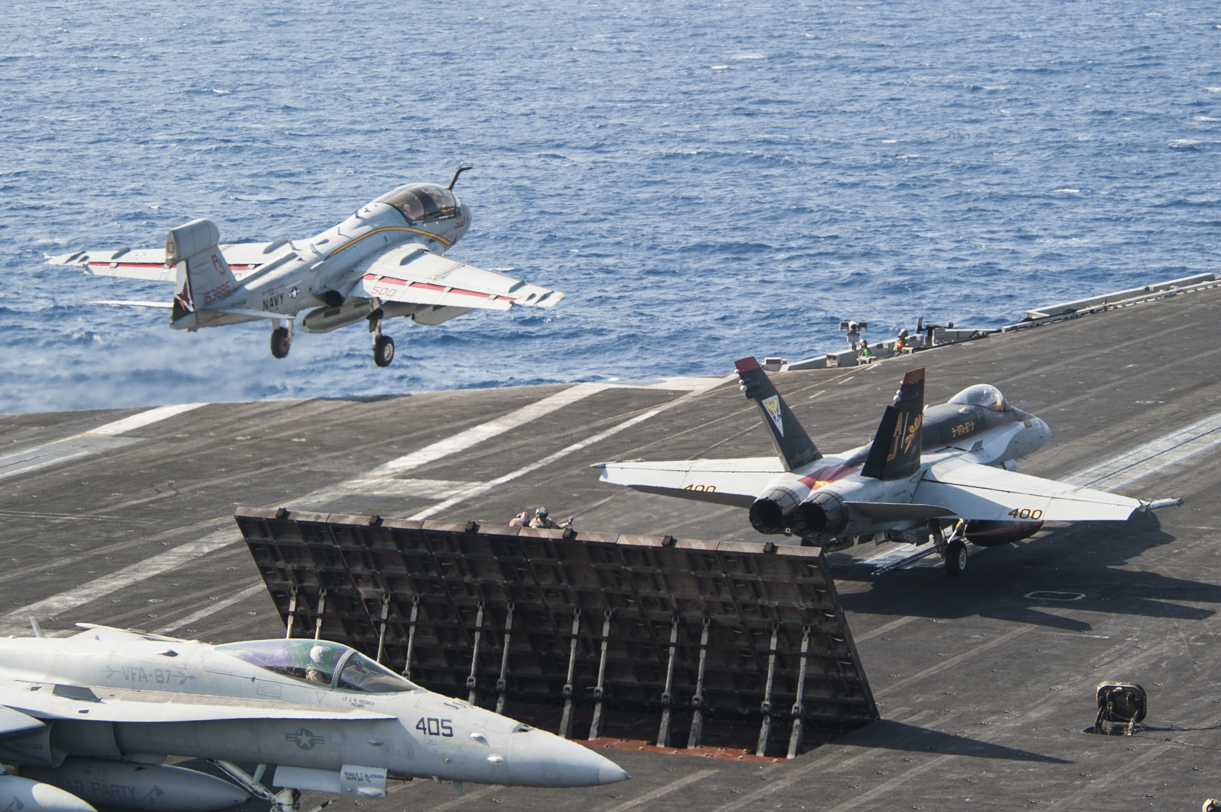 "An EA-6B Prowler, attached to the ""Garudas"" of Electronic Attack Squadron (VAQ) 134, left, and an F/A-18C Hornet, attached to the ""Golden Warriors"" of Strike Fighter Squadron (VFA) 87, take off from the flight deck of the aircraft carrier USS George H.W. Bush (CVN 77) on Oct. 25, 2014. US Navy photo."