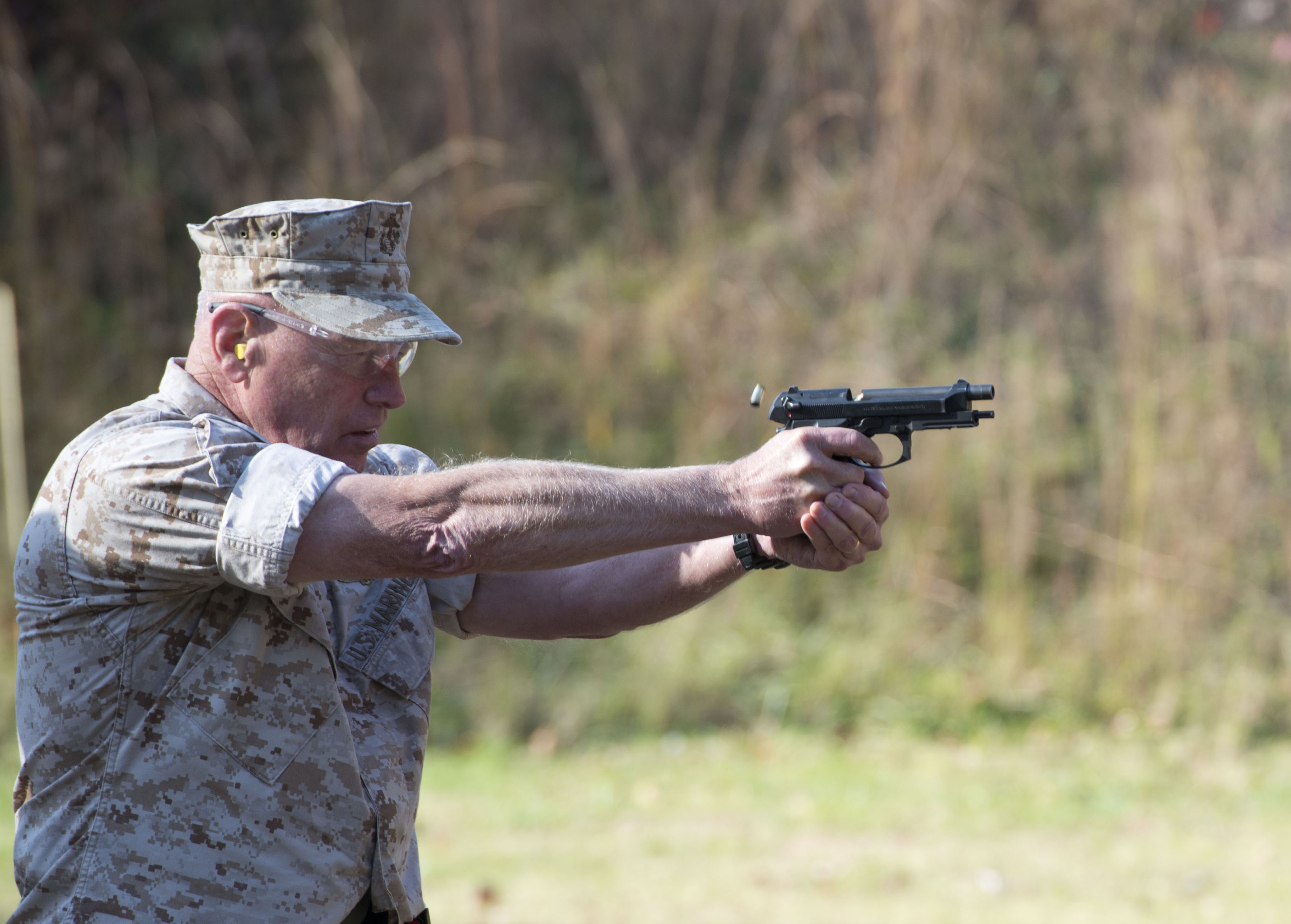 Lieutenant Gen. Kenneth J. Glueck, Jr., fires a M9 pistol during the 4th Annual Quantico Combat Shooting Match Oct. 29, 2014. US Marine Corps Photo