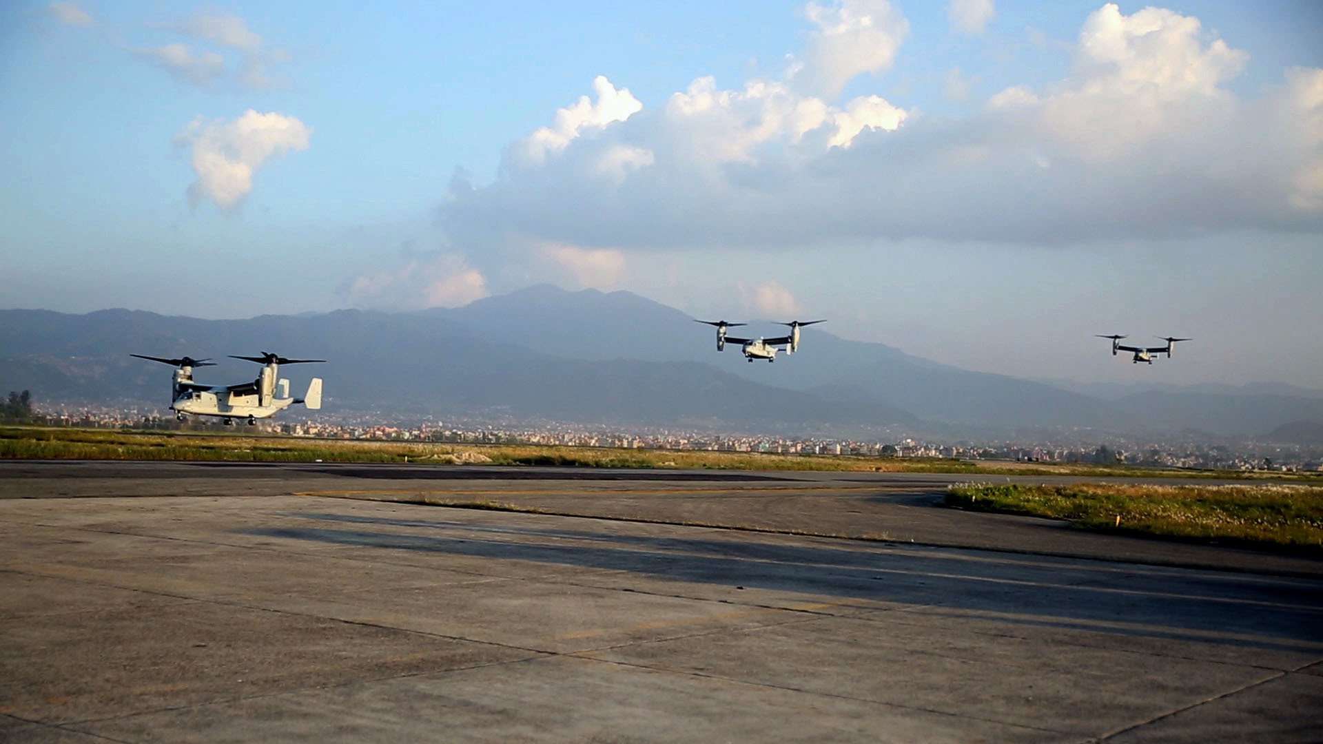 U.S. Marine V-22 Ospreys fly into Tribhuvan International Airport in Kathmandu, Nepal, May 3. U.S. Marines also brought an UH-1N Huey, tools and equipment to support the government of Nepal. The Nepalese Government requested the U.S. Government's help after a 7.8 magnitude earthquake struck their country, April 25. The Marines are with Marine All-Weather Fighter Attack Squadron 242, Marine Aircraft Group 12, I Marine Aircraft Wing, III Marine Expeditionary Force. (U.S. Marine Corps photo by Lance Cpl. Mandaline Hatch/Released)