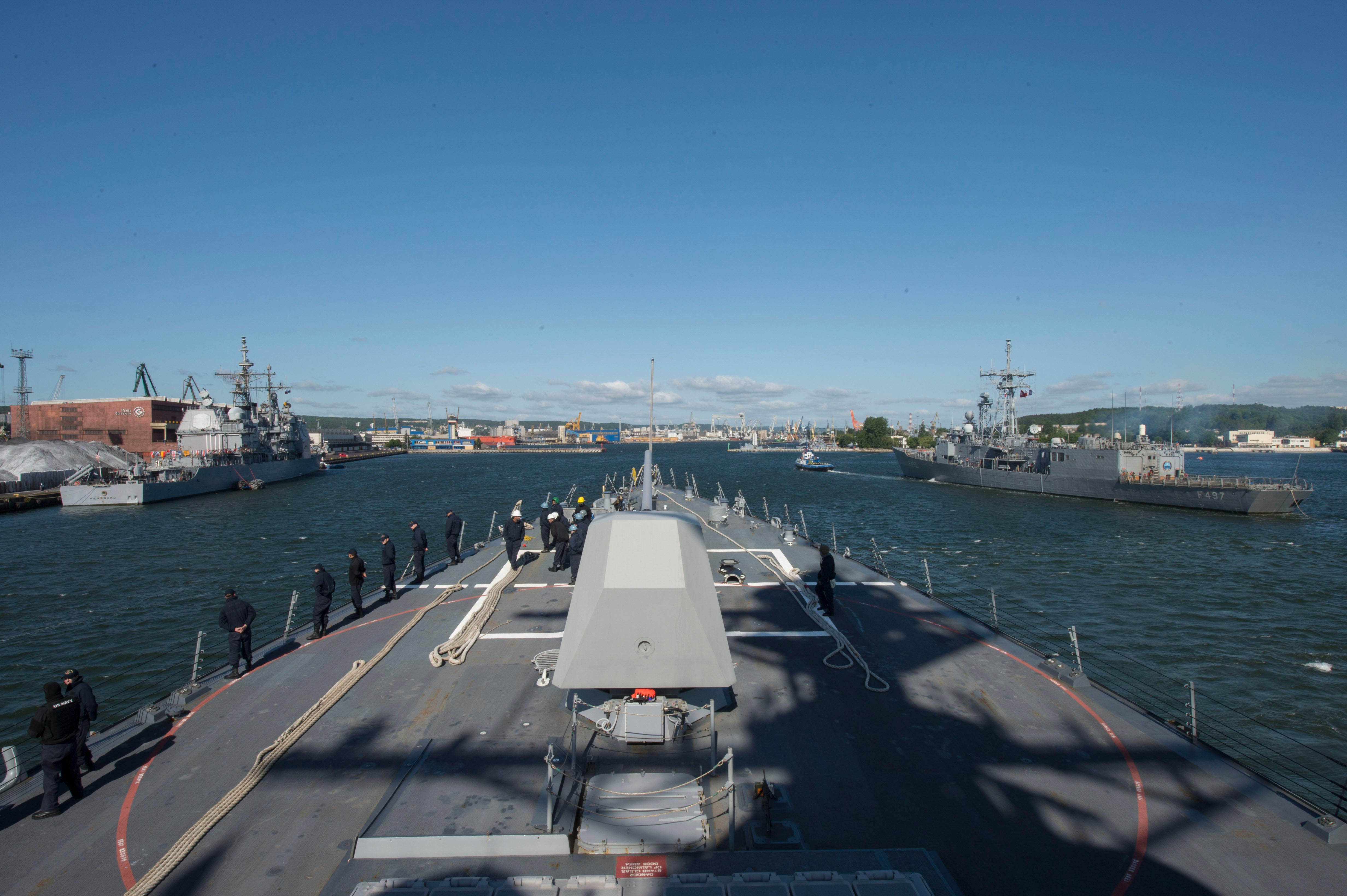 The guided-missile destroyer USS Jason Dunham (DDG 109) maneuvers into port in Gdynia, Poland, outboard of the guided-missile cruiser USS Vicksburg (CG 69) while the Turkish navy ship TCG Göksu (F 497) passes on the starboard side on June 4, 2015. US Navy photo.