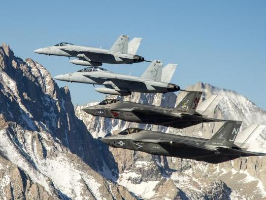 Two F-35C Lightning II aircraft fly in formation over the Sierra Nevada mountain range with to two F/A-18E/F Super Hornets. US Navy Photo
