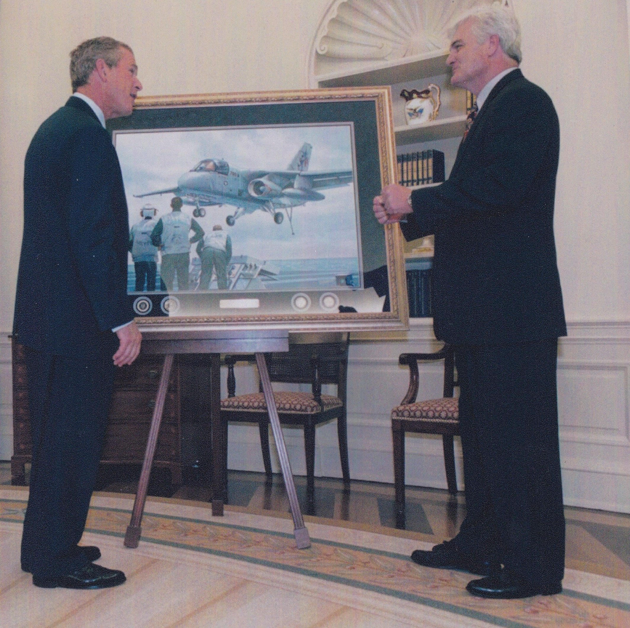 "Tom Freeman presents ""A Presidential First"" to President George W. Bush at the White House. The painting shows the President landing in an S-3 aboard the USS Abraham Lincoln (CVN-72) on 1 May 2003. US Naval Institute Photo"