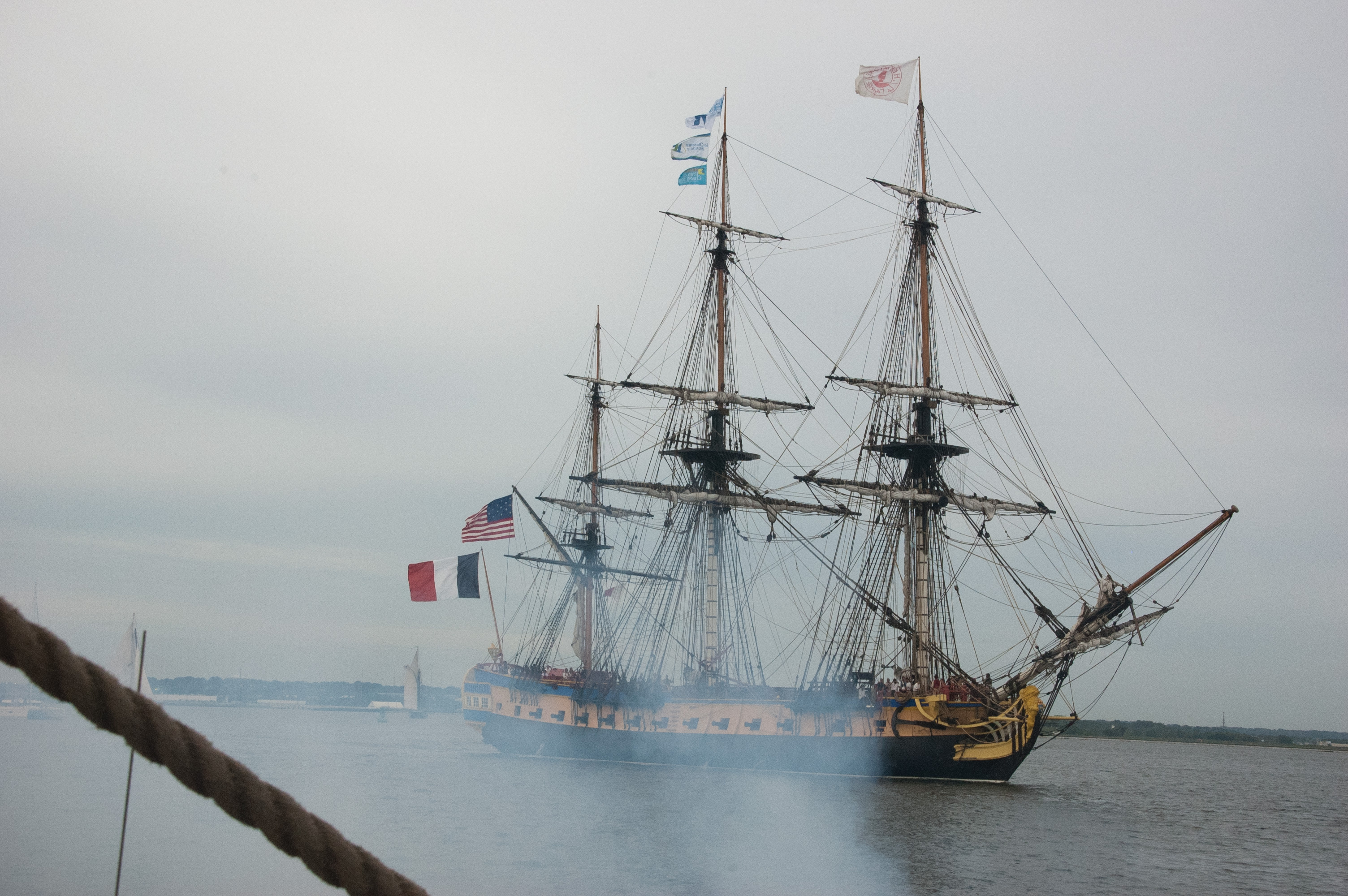 The replica French frigate Hermione shot several blank rounds to greet Baltimore as it sailed into the Inner Harbor. USNI News photo.
