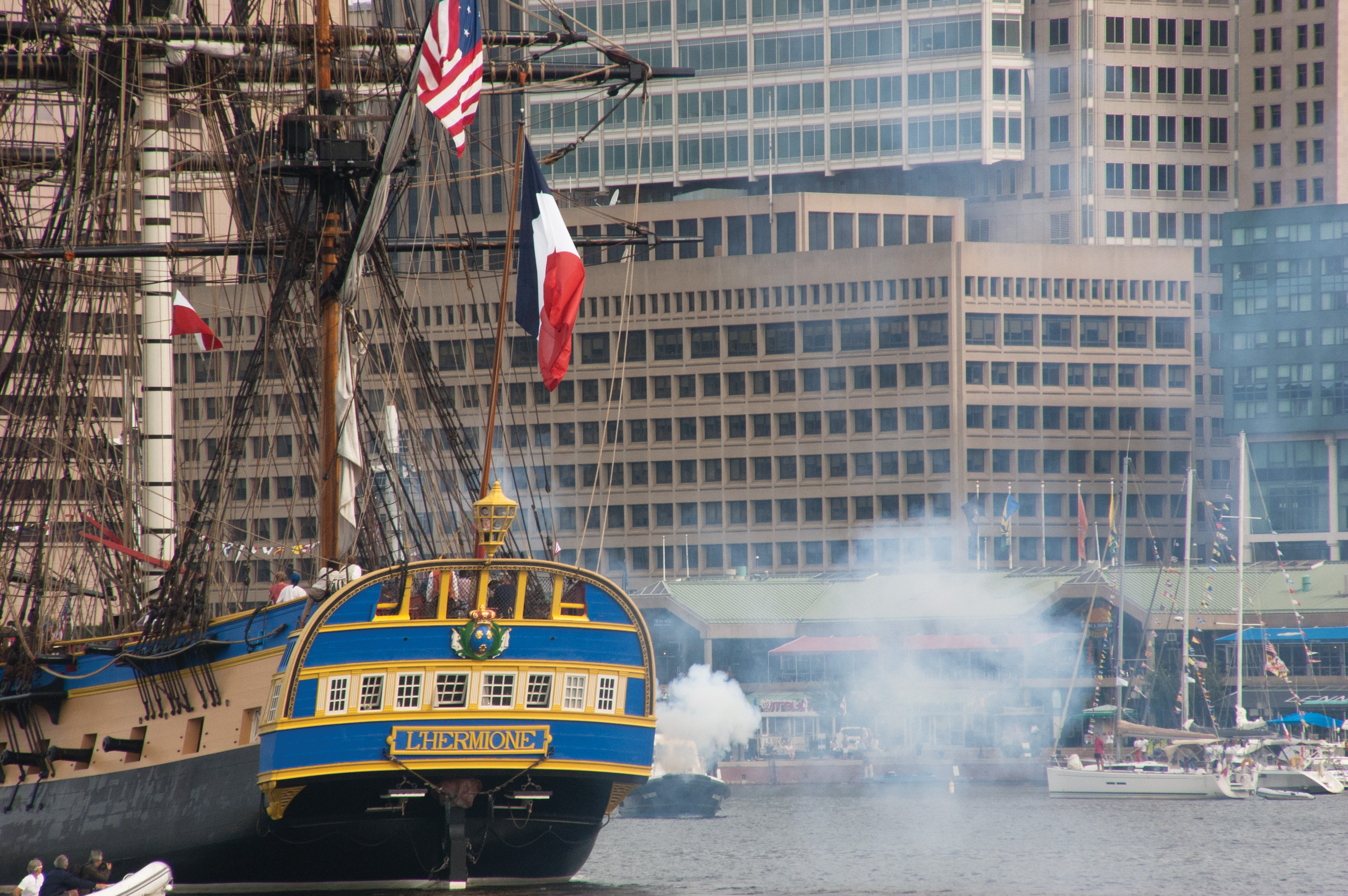 The replica Hermione fires a series of blank rounds to greet the city of Baltimore. USNI News photo.