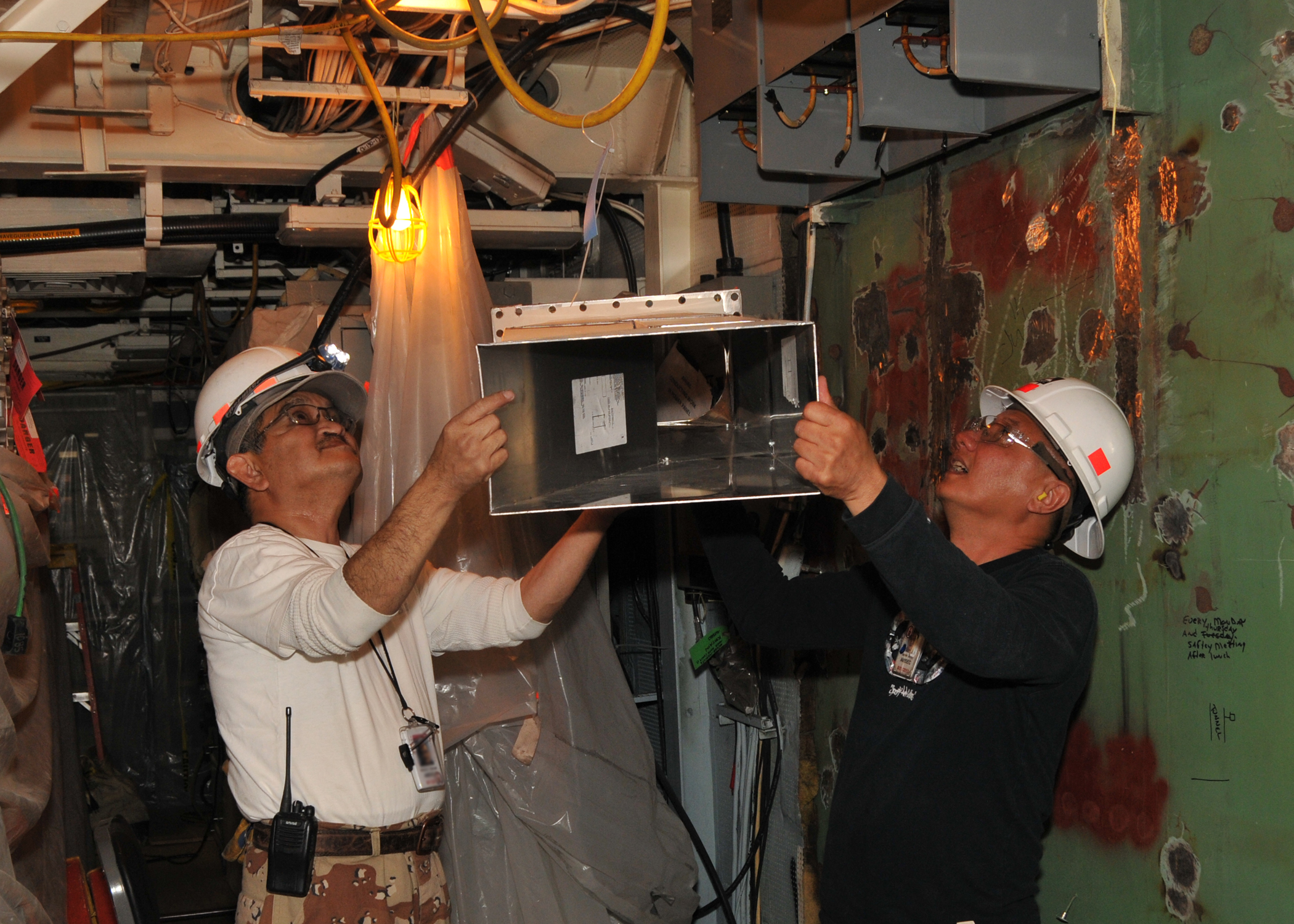 AMSEC contractors remove ventilation in the radio room onboard the Navy guided missile destroyer USS Milius (DDG 69) in March 2013. US Navy photo.