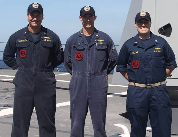 Three Intergrated Air and Missile Defense Warfare Tactics Instructors (WTIs) displaying their WTI patches during an April exercise. US Navy Photo