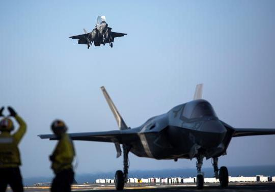 A sailor aboard the USS Wasp (LHD-1) signals to the pilot of an F-35B to land as it arrives for the first phase of operational testing, May 18, 2015. US Marine Corps photo.