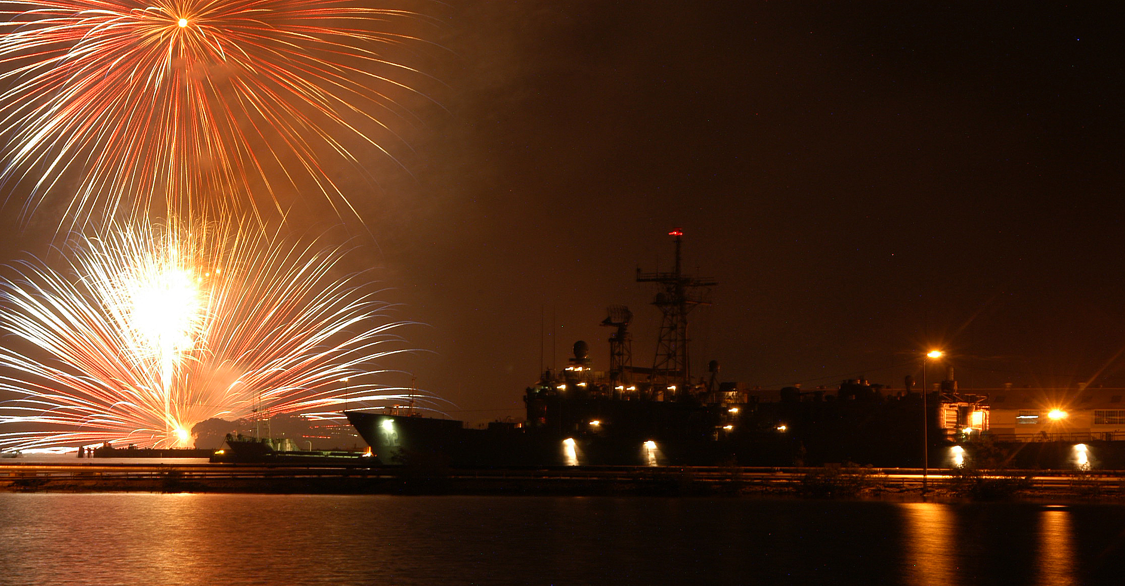 Fireworks explode above frigate USS John L. Hall (FFG-32) while moored pierside at U.S. Naval Station, Guantanamo Bay during an Independence Day celebration in 2004. US Navy Photo