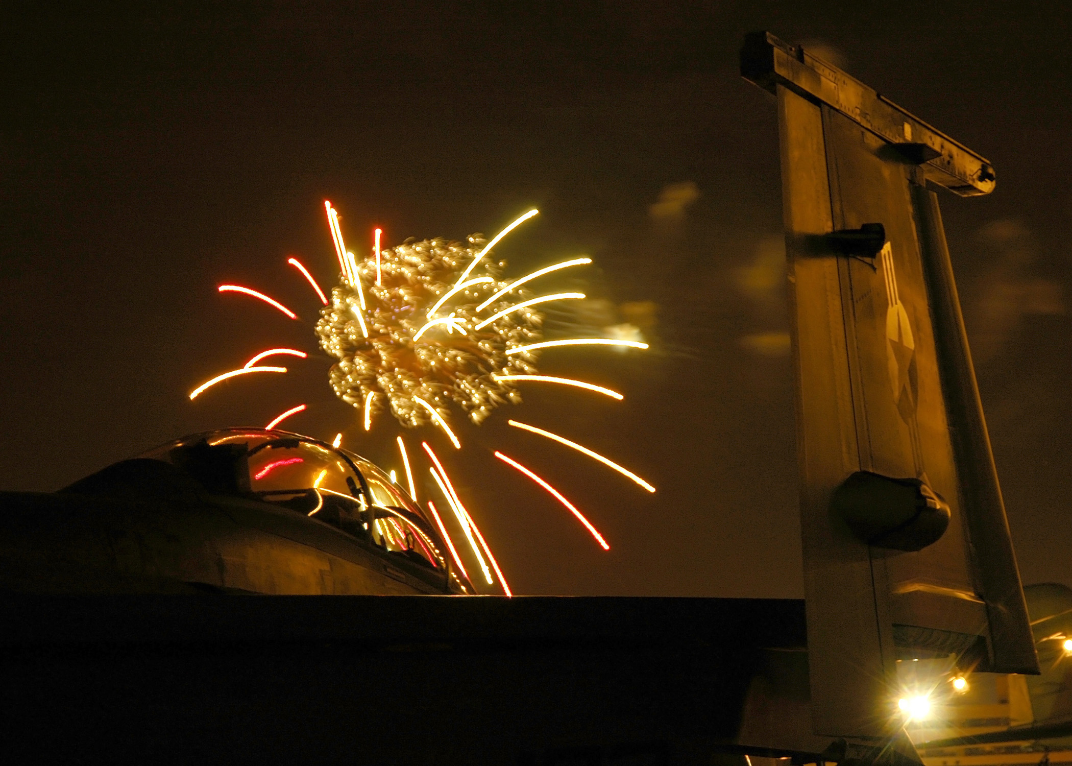 Fireworks explode over an F/A-18F Super Hornet on the flight deck of the Nimitz-class aircraft carrier USS Abraham Lincoln (CVN-72) during an Independence Day celebration at Naval Station Pearl Harbor in 2006. US Navy Photo
