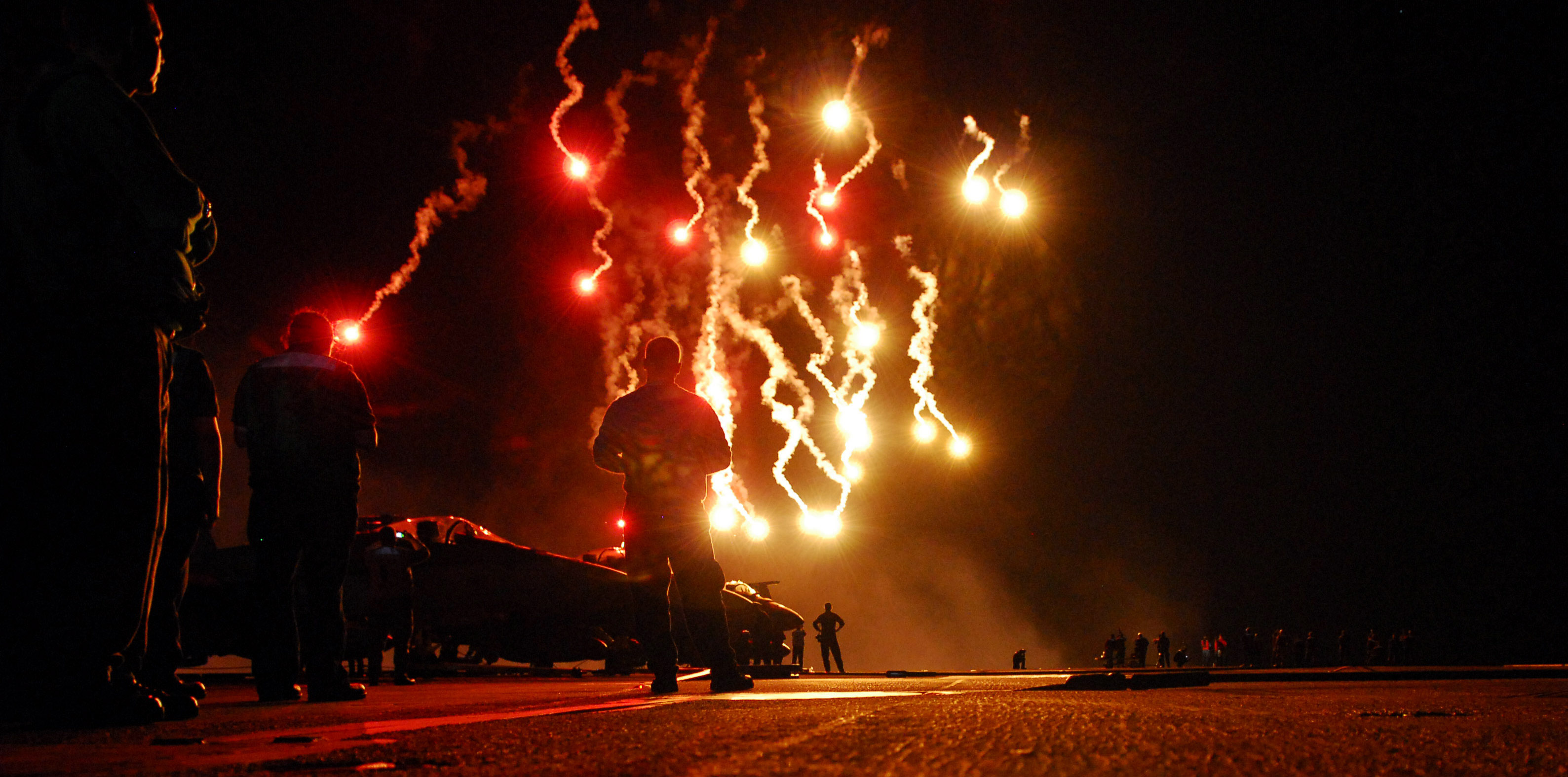 Sailors watch flares light up the sky during a Navy-style fireworks display on the flight deck of the Nimitz-class aircraft carrier USS Ronald Reagan (CVN-76) in 2008. US Navy Photo