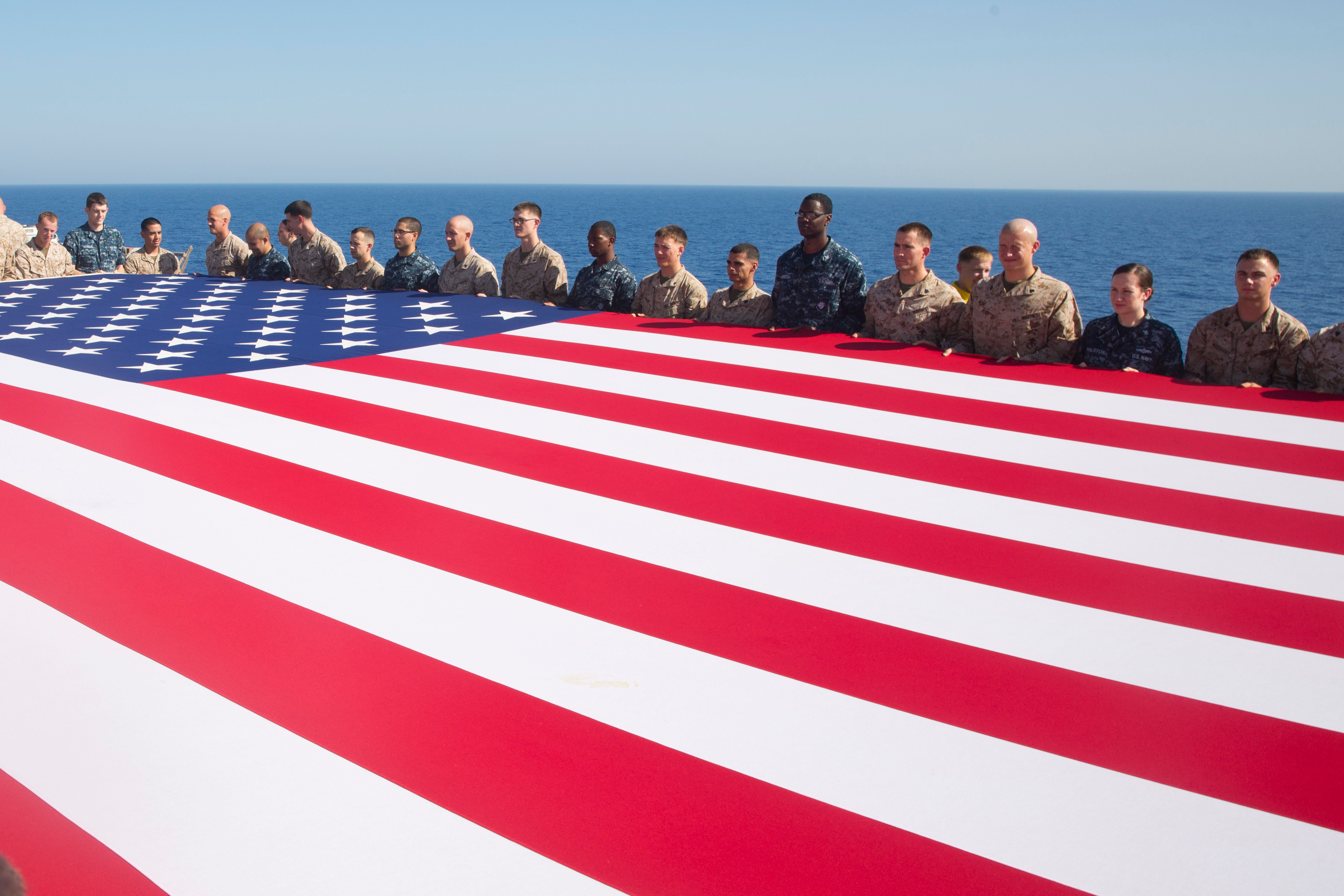 Sailors and Marines display the national ensign in honor of Independence Day aboard the amphibious assault ship USS Kearsarge (LHD 3) in 2013. US Navy Photo