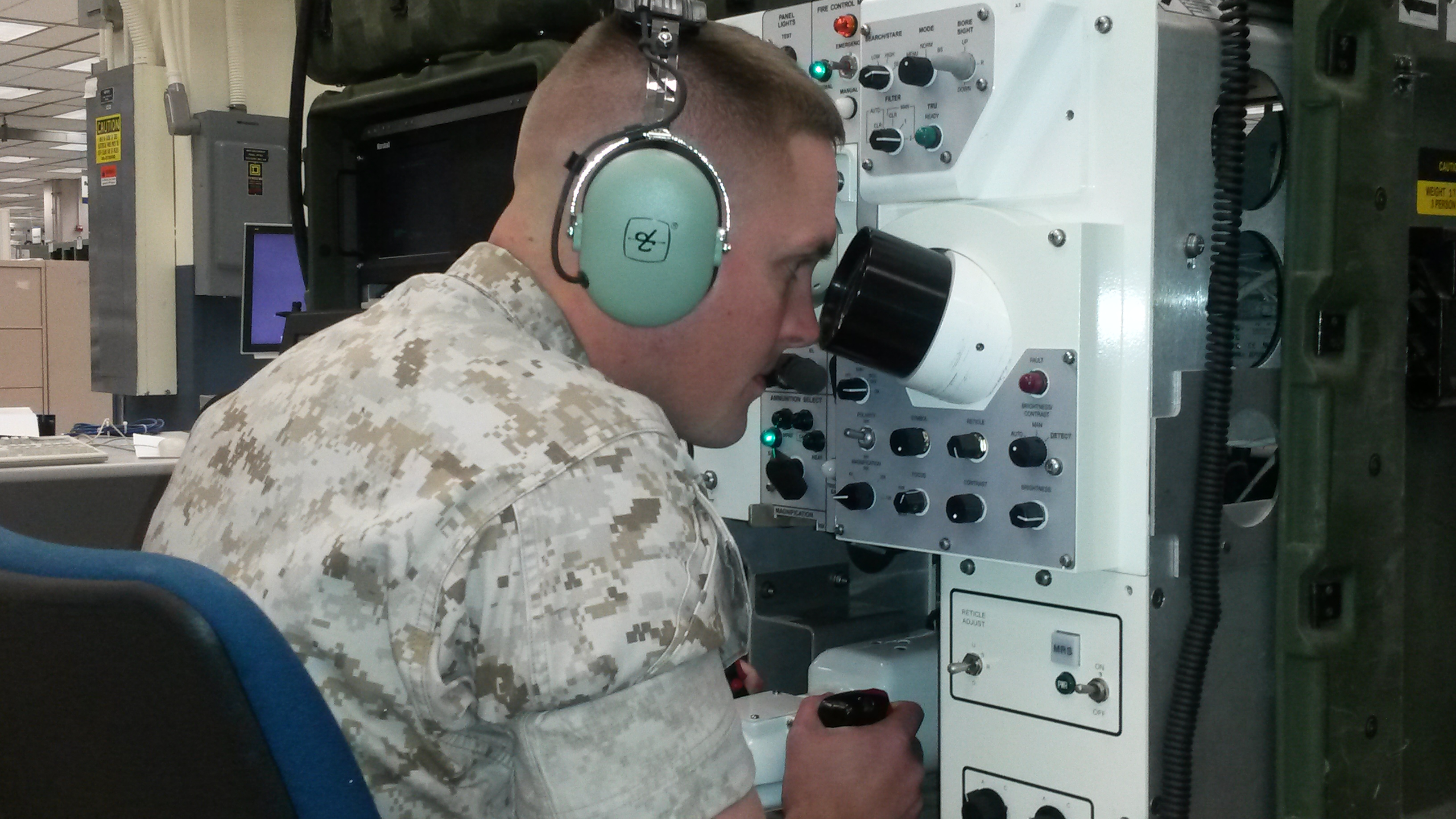 1st Lt. M. Joel Wagaman, project manager at Marine Corps Systems Command's Program Manager Training Systems, demonstrates the use of the Advanced Gunnery Training System—a simulation-based system that provides Marine crews gunnery and tactical training for the M1A1 Main Battle Tank and Light Armored Vehicle. US Marine Corps photo.