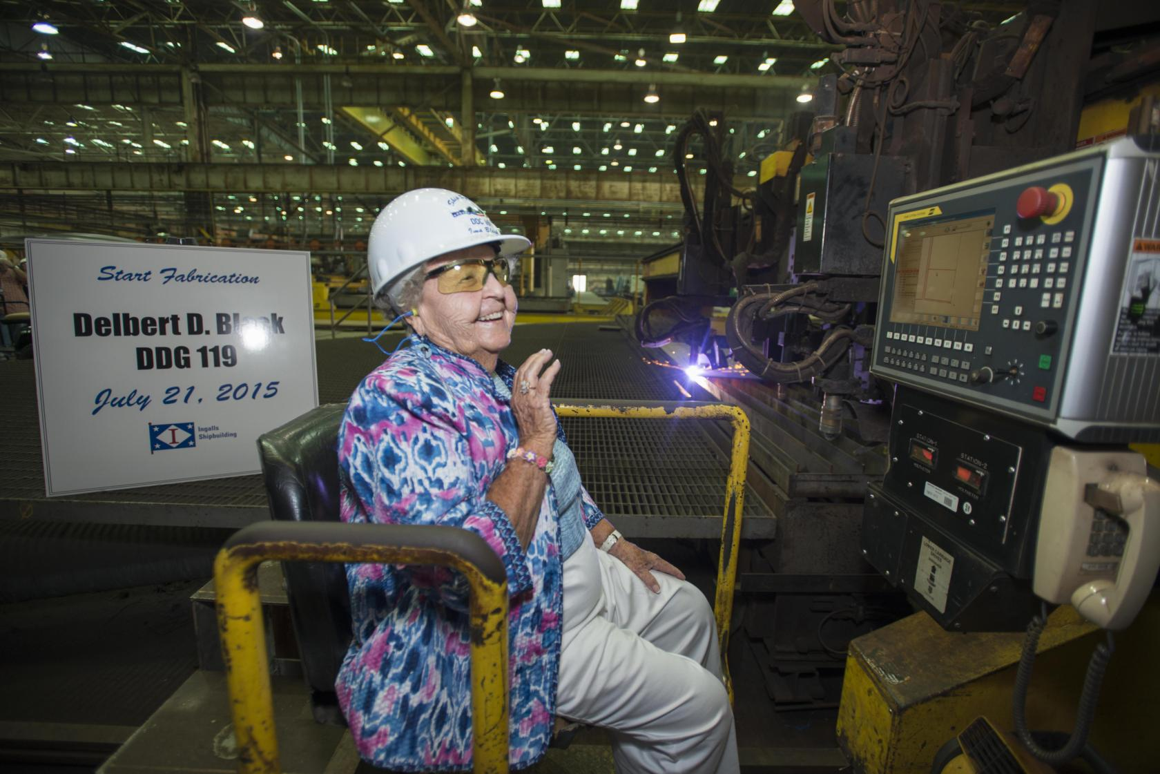 Ima Black reacts after starting a plasma cutter machine at Ingalls Shipbuilding, officially beginning construction of the Arleigh Burke-class destroyer Delbert D. Black (DDG 119), which is named in honor of her late husband. HII Photo