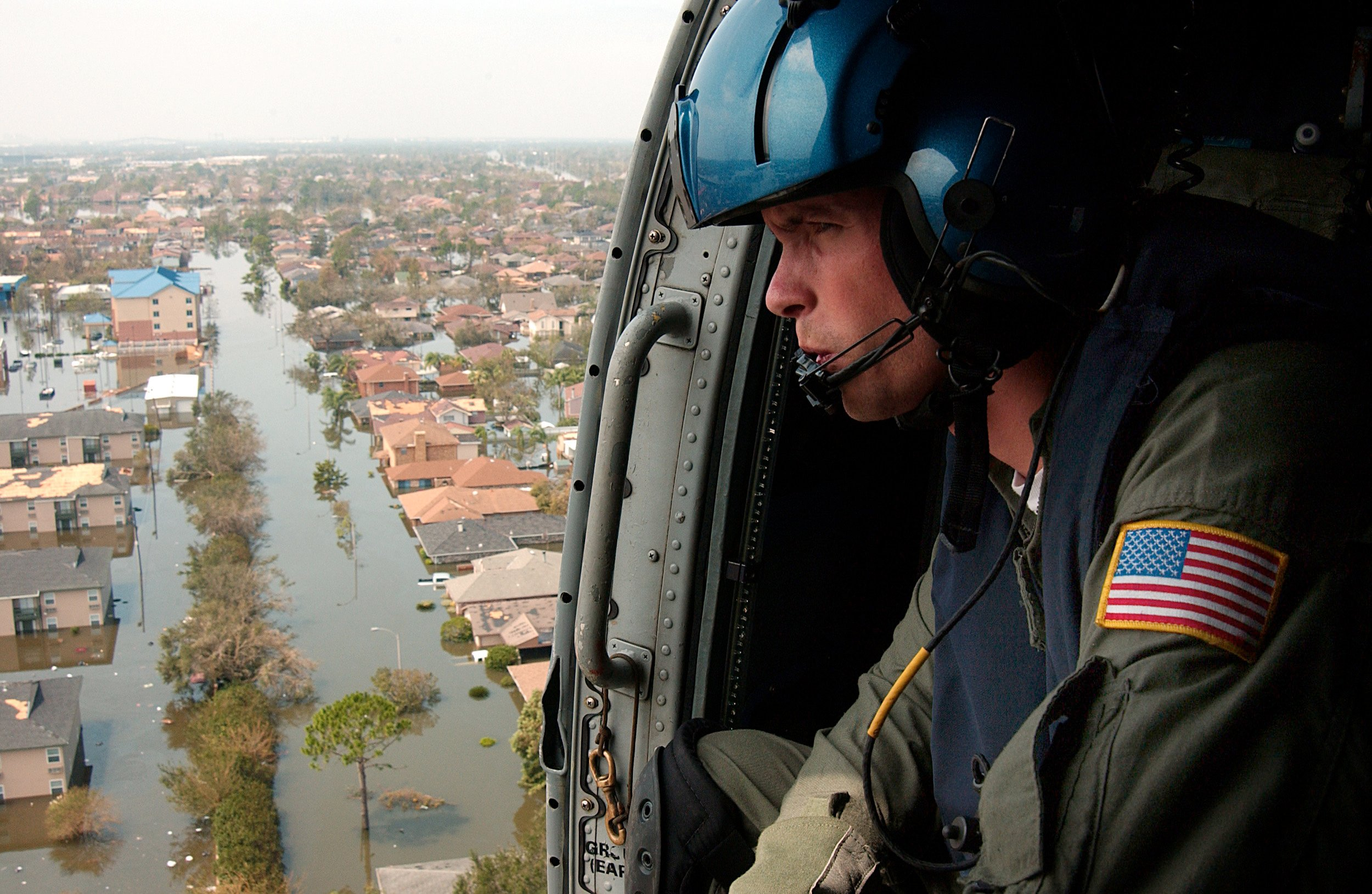 U.S. Coast Guard Petty Officer 2nd Class Shawn Beaty of Long Island, N.Y., looks for survivors in the wake of Hurricane Katrina as he flies in a HH-60J Jayhawk helicopter over New Orleans on Aug. 30, 2015. US Coast Guard Photo
