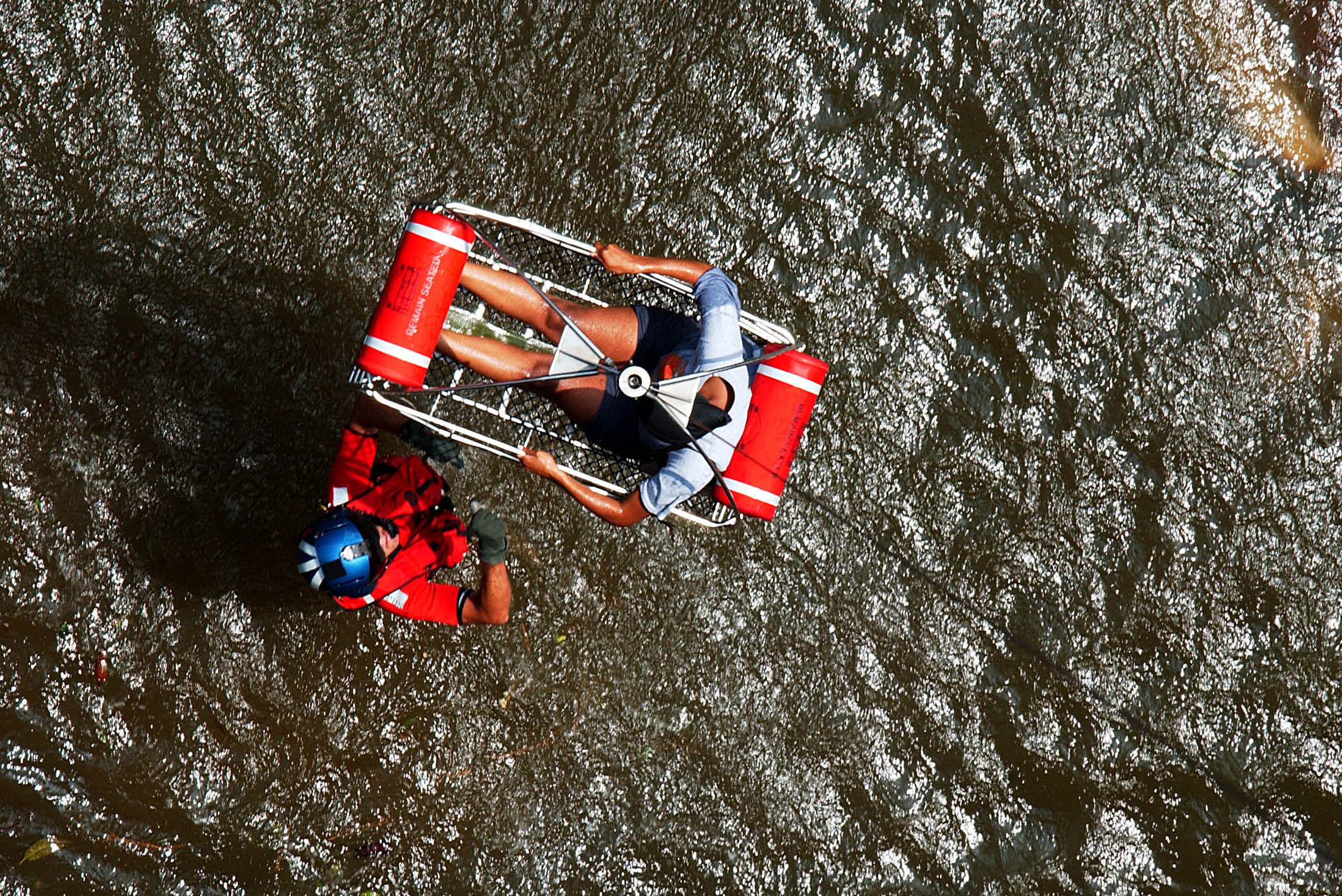 U.S. Coast Guard Petty Officer 2nd Class Scott D. Rady of Tampa, Fla., gives the signal to hoist-up a pregnant woman from her apartment during a search and rescue (SAR) flight in New Orleans on Aug. 31, 2005. US Coast Guard Photo