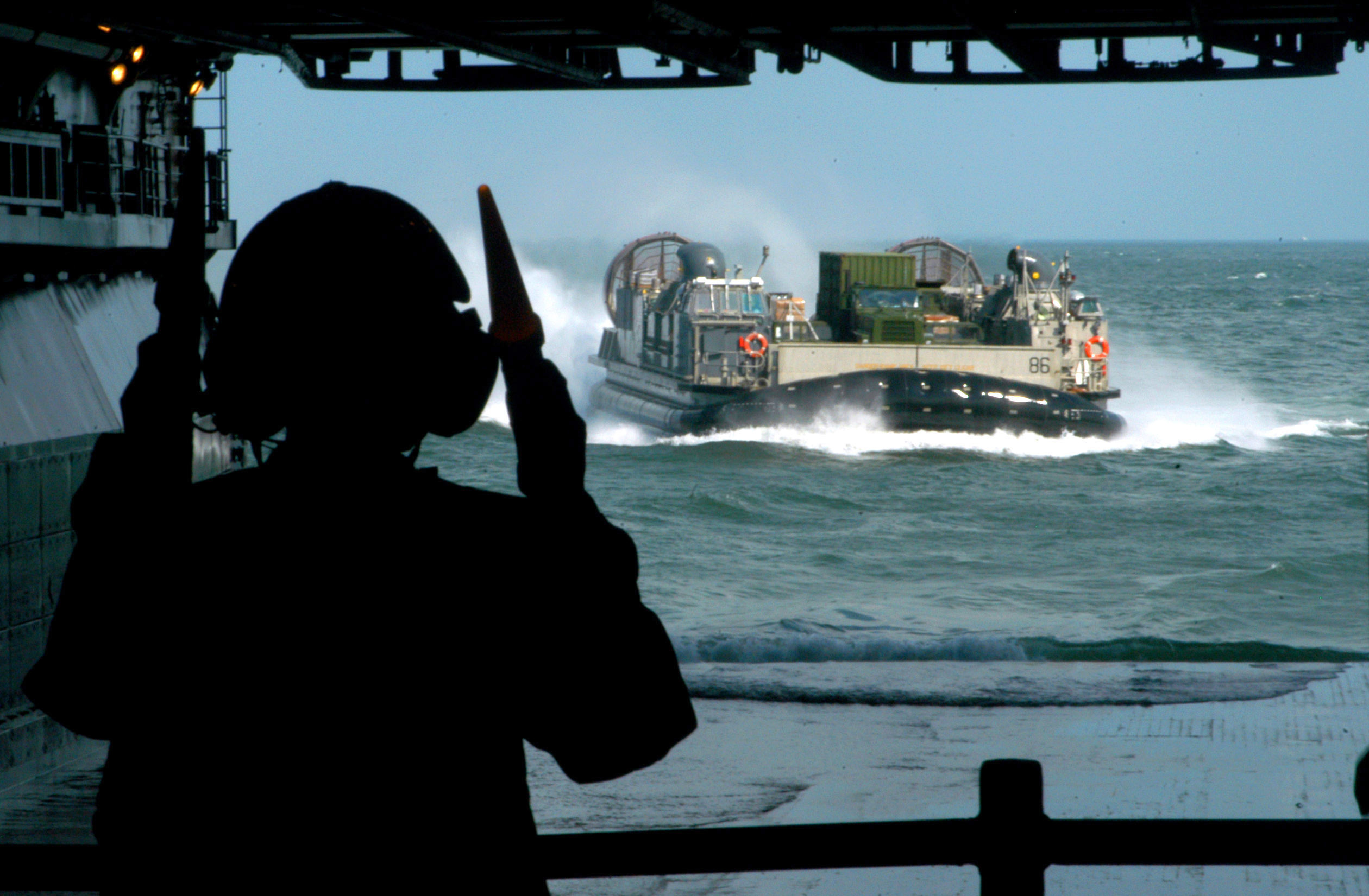 Boatswain's Mate Seaman  Whitney Clark directs a Landing Craft, Air Cushion (LCAC) into the well deck of the amphibious assault ship USS Iwo Jima (LHD 7). Iwo Jima on Aug. 31, 2005. US Navy Photo