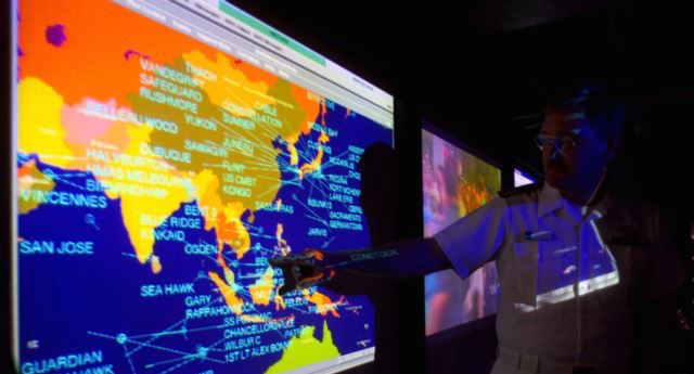 Lt. Cmdr. Kirk Benson, points at a map of the South China sea at the Tactical Flag Command Center (TFCC) of the USS Blue Ridge. Reuters photo via VOA.