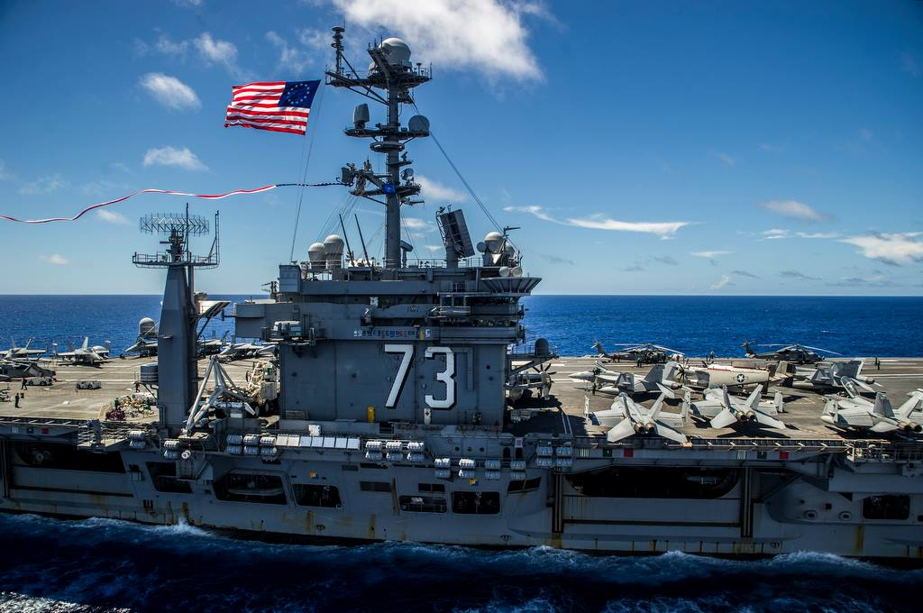 The Nimitz-class aircraft carrier USS George Washington (CVN-73) flies the U.S. Navy battle ensign and the 297-foot Homeward Bound Pennant on July 27, 2015, as it sails through the Western Pacific on its way to San Diego. The Homeward Bound Pennant is flown by ships that are on a continuous overseas duty for 9 months and returning to a U.S. port. US Navy photo.