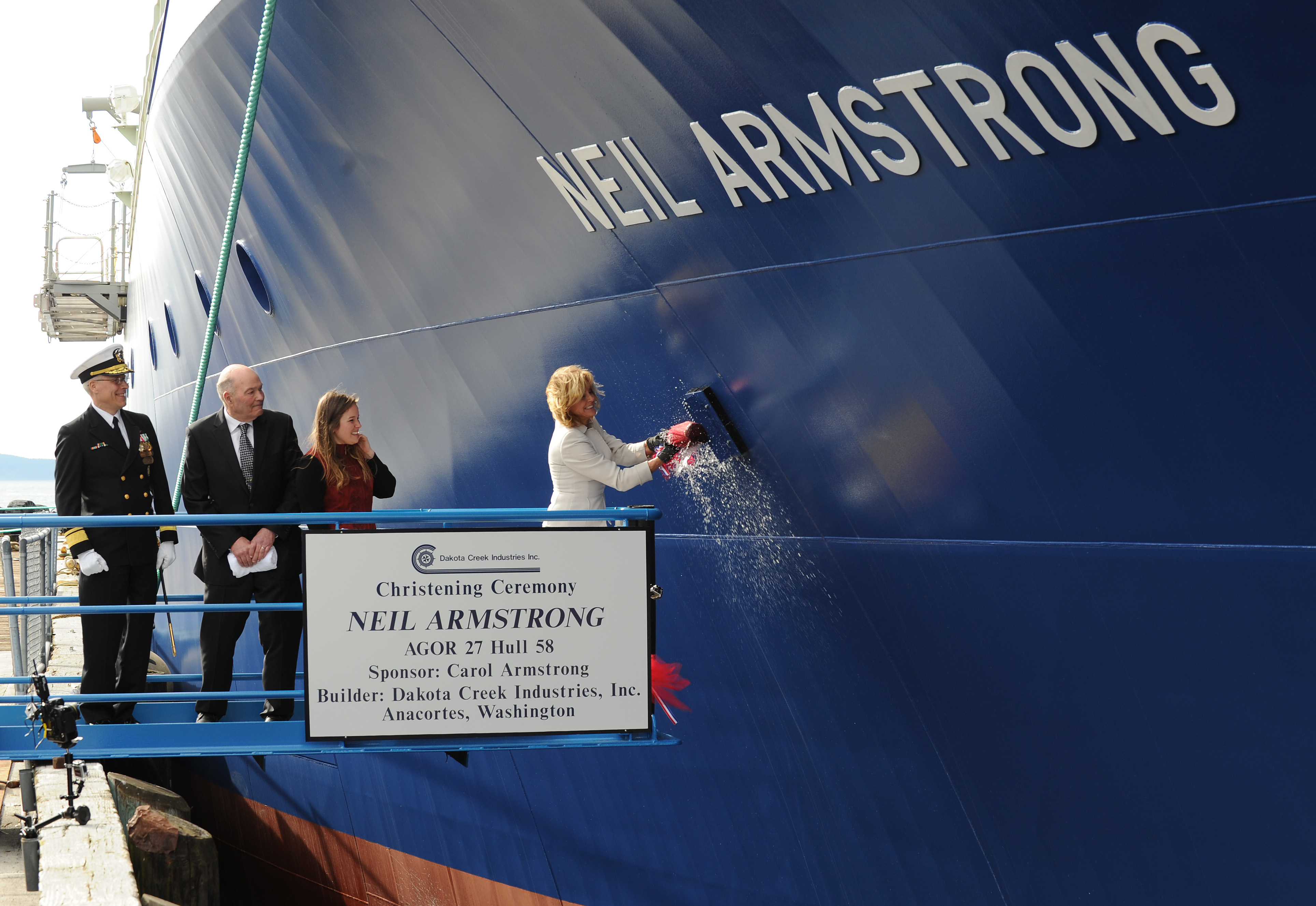Carol Armstrong, ship's sponsor for the Auxiliary General Oceanographic Research (AGOR) research vessel (R/V) Neil Armstrong (AGOR 27), breaks a bottle across bow during a 2014 christening ceremony at Dakota Creek Industries, Inc., shipyard in Anacortes, Wash. US Navy photo.